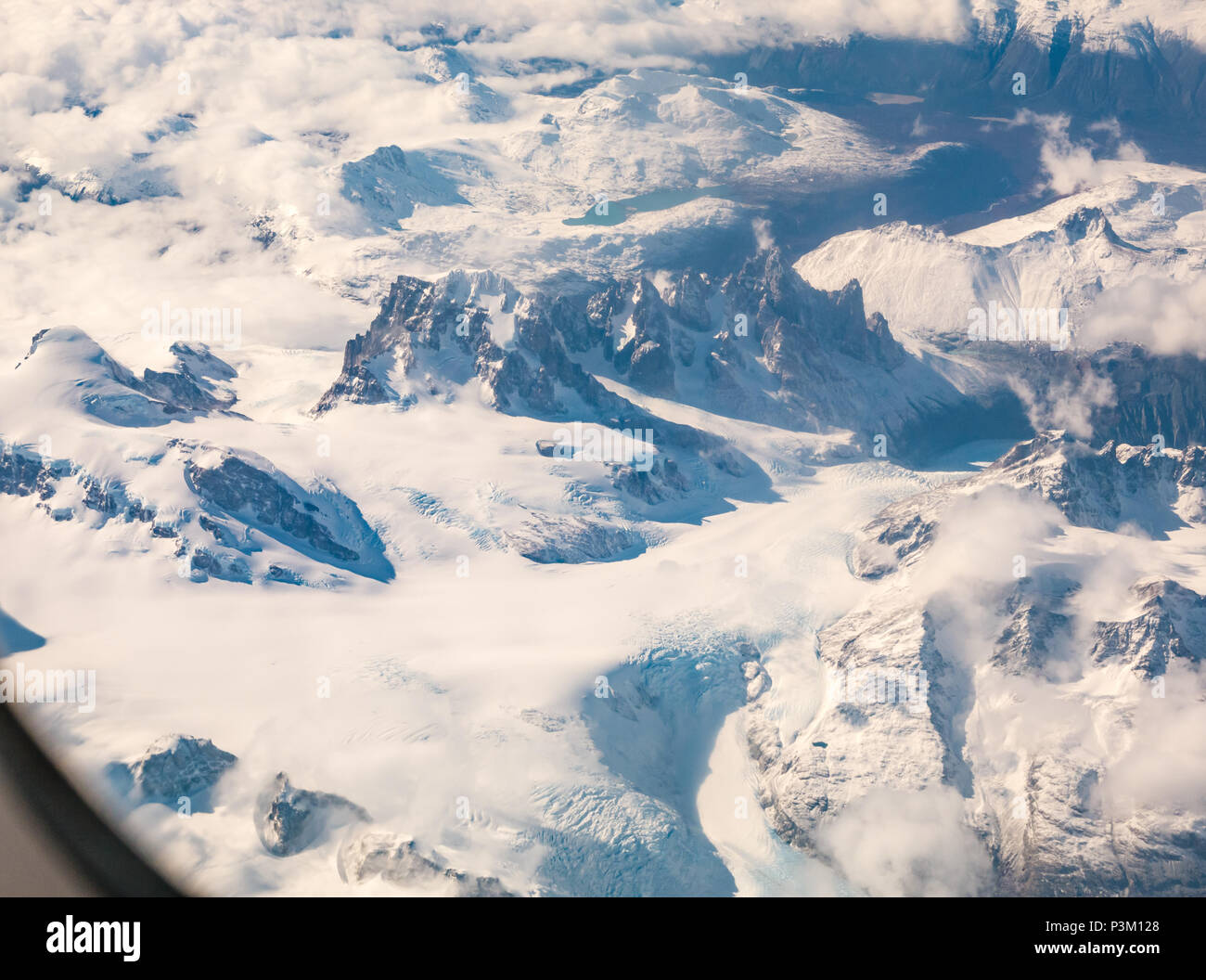 View from aeroplane window of snow covered Andes mountain peaks with glaciers, Southern Patagonian Ice field, Patagonia, Chile, South America - Stock Image
