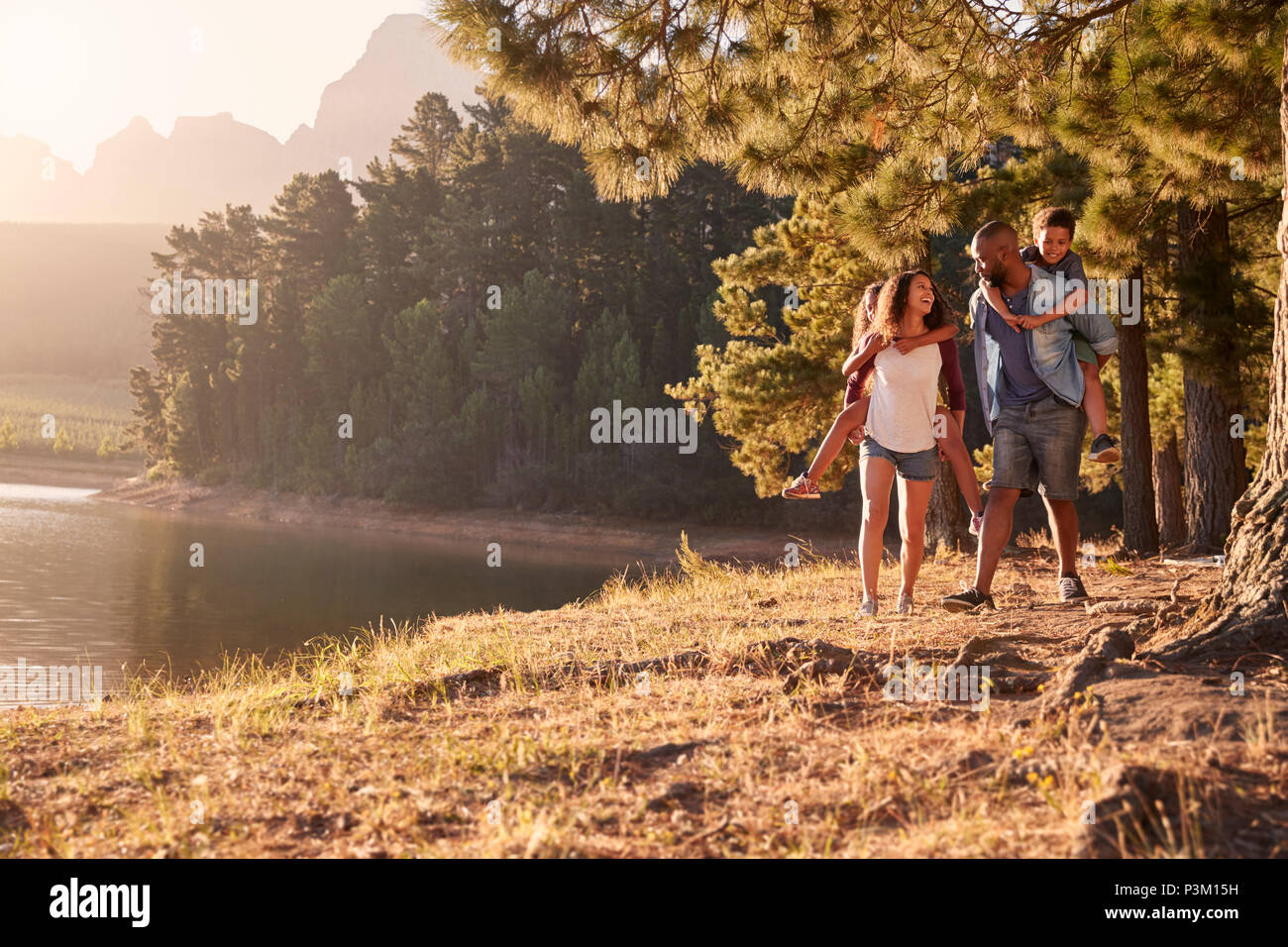Parents Giving Children Piggyback Rides On Walk By Lake - Stock Image