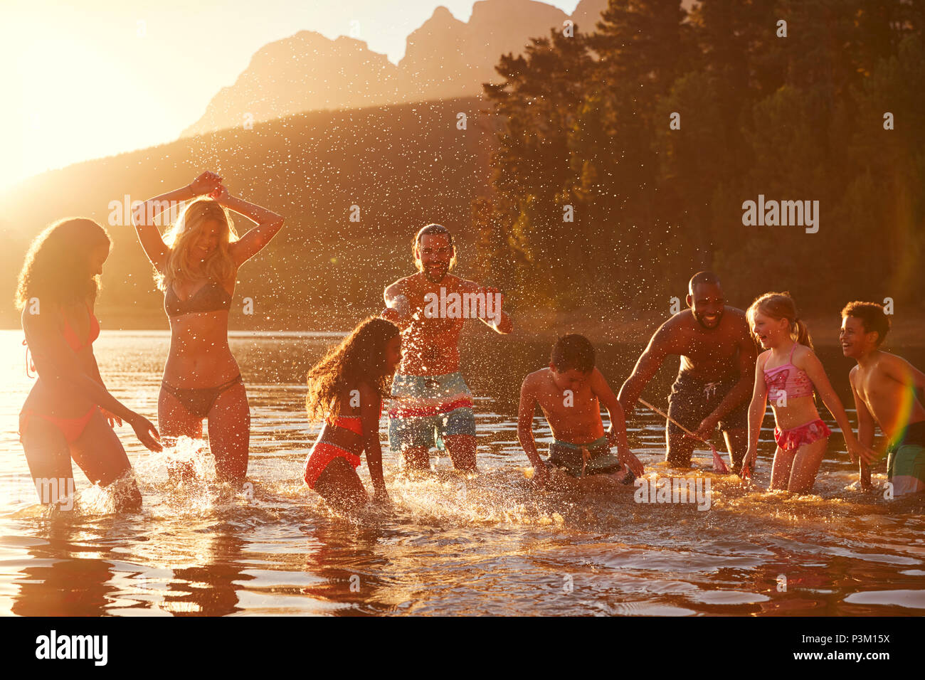 Family With Friends Enjoying Evening Swim In Countryside Lake - Stock Image