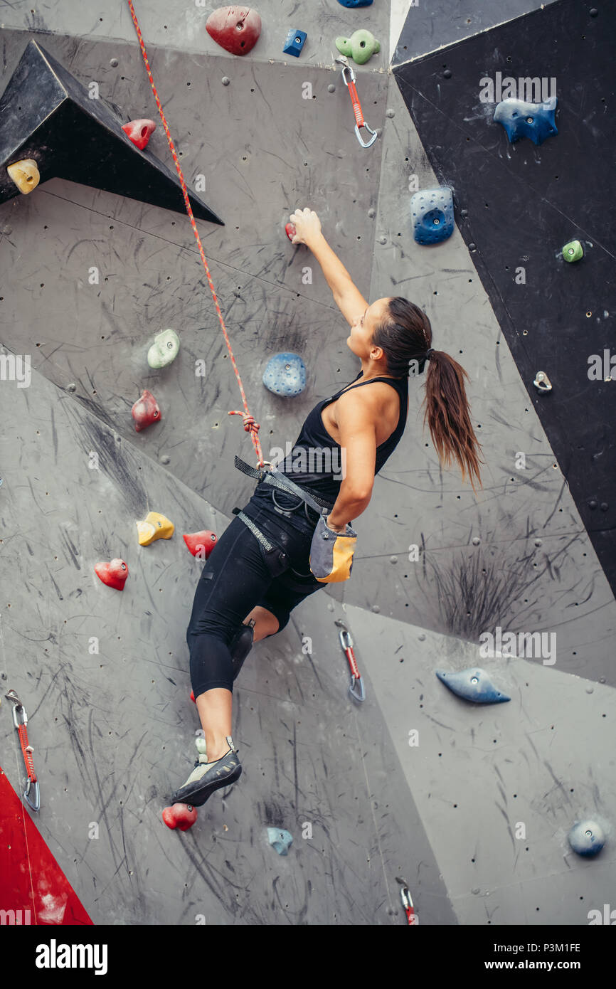 sporty woman in boulder climbing hall - Stock Image