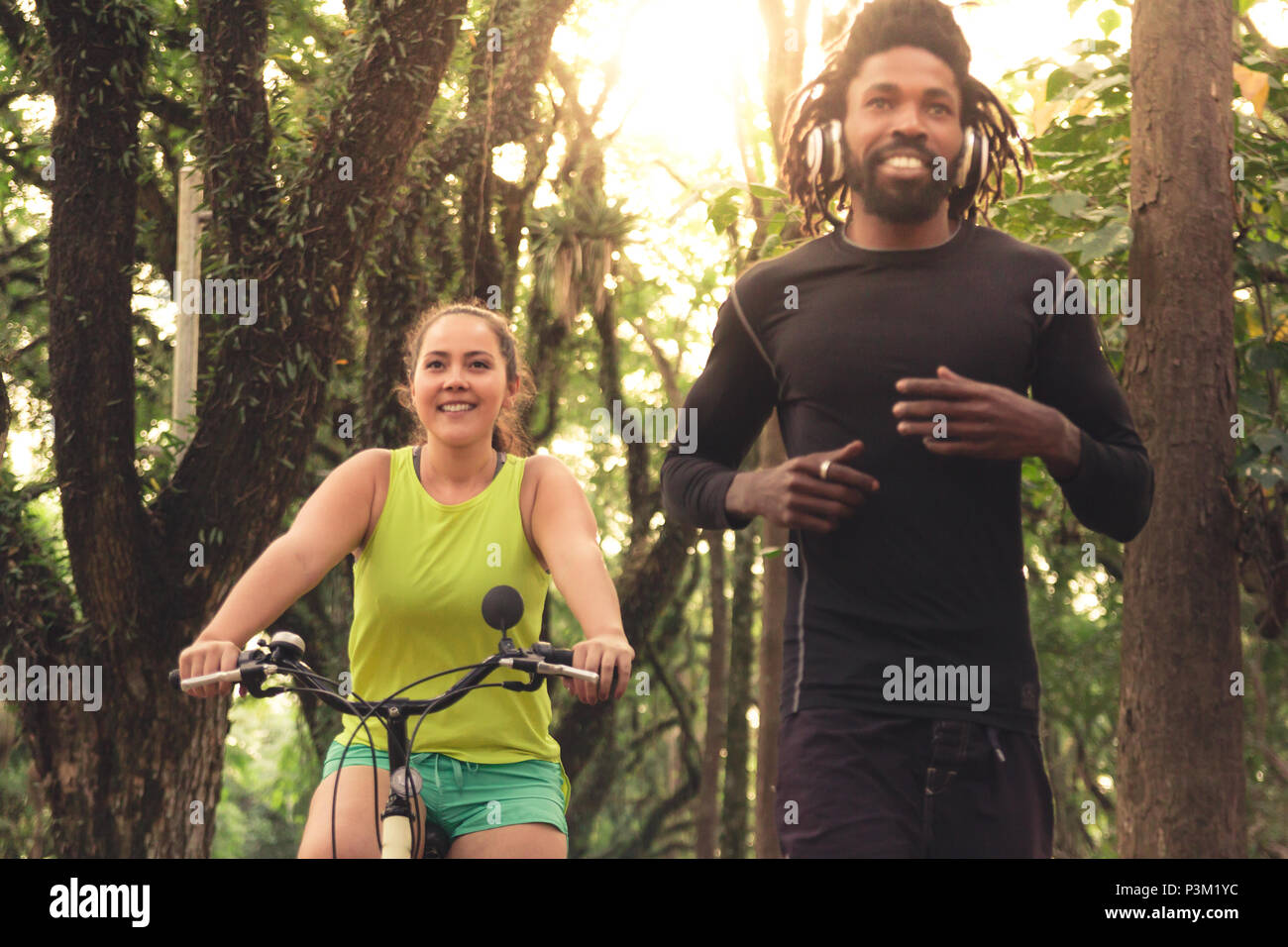 Asian woman is riding a bike and african american man is running in woodland. Multiracial couple exercising. Healthy lifestyle and sport concept - Stock Image