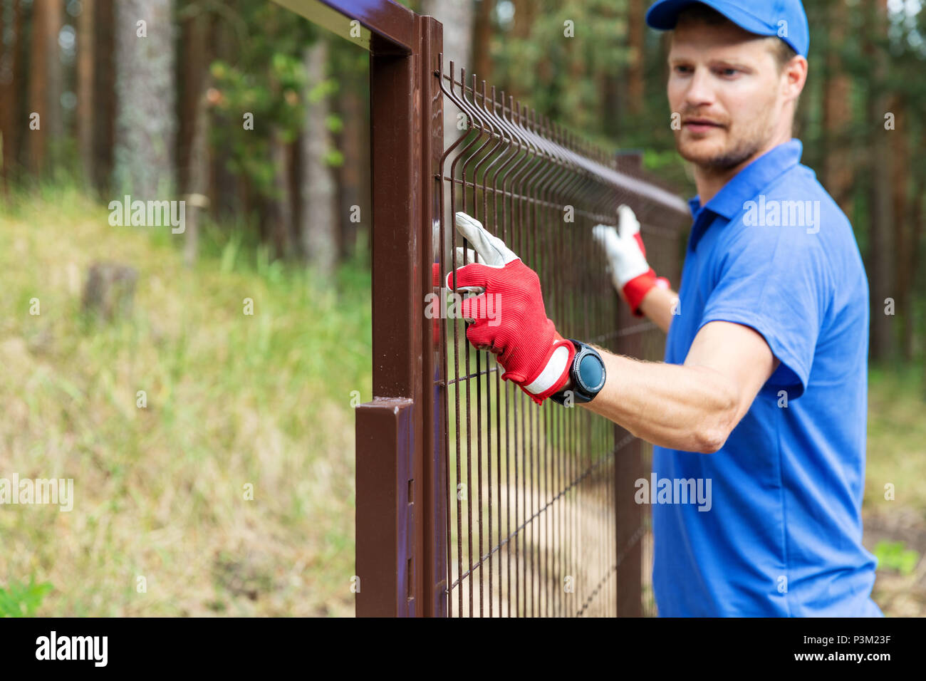worker installing welded metal mesh fence Stock Photo
