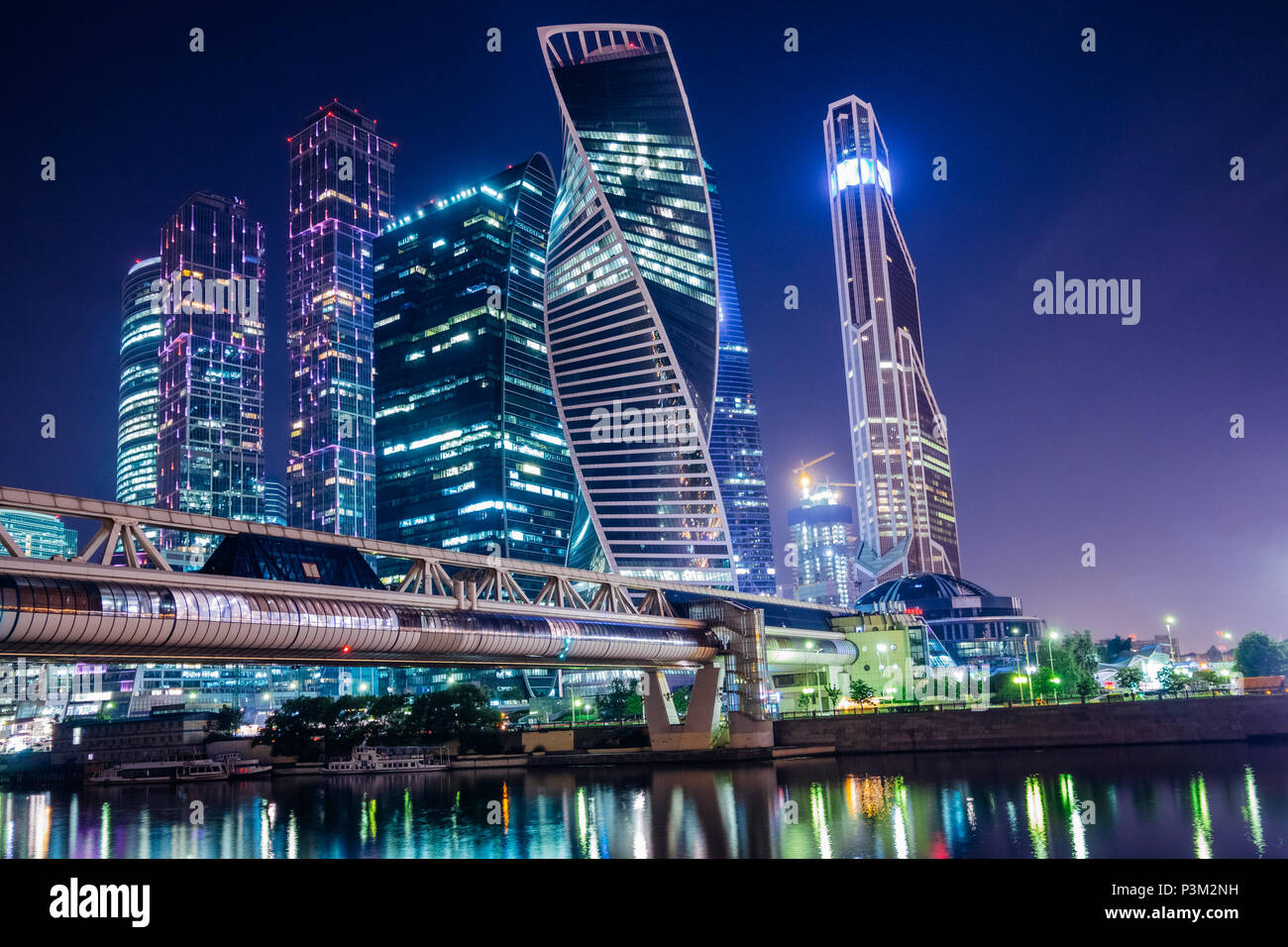 Modern skyscrapers of Moscow at night with a bridge across the river with illumination - Stock Image