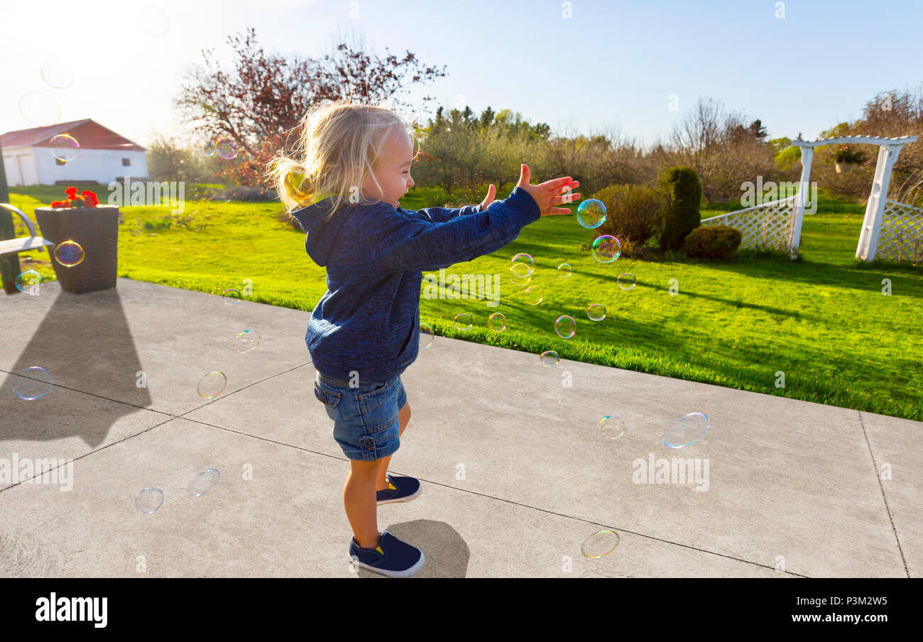 Caucasian toddler playing with soap bubbles outdoors - Stock Image