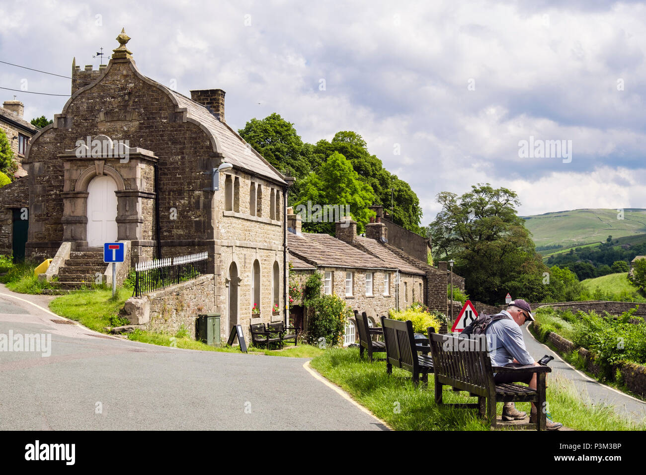 Walker resting on a bench by Muker Literary Institute in Yorkshire Dales National Park village of Muker Swaledale North Yorkshire England UK Britain - Stock Image