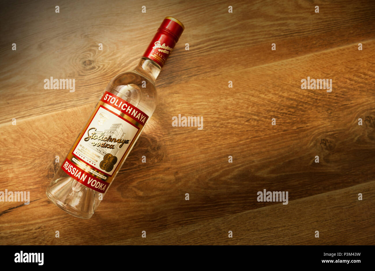 Chisinau, Moldova 18 June 2018: A bottle of Stolichnaya vodka on an wooden background. Russian traditional alcoholic beverage, produced in Russia at C - Stock Image