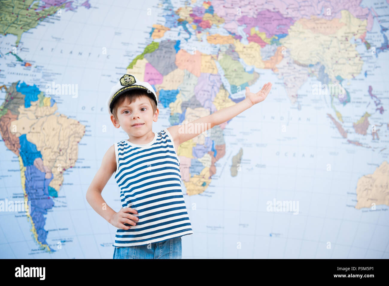 handsome happy small boy in captain hat offer travel world map background - Stock Image