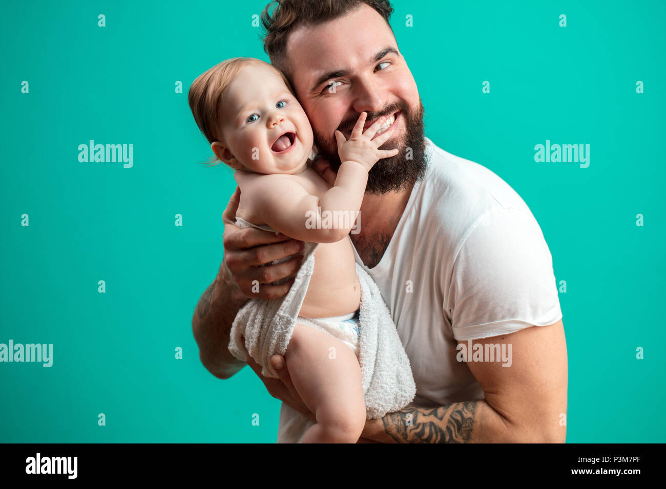 Playful father carrying his smiling infant child on neck over blue background - Stock Image