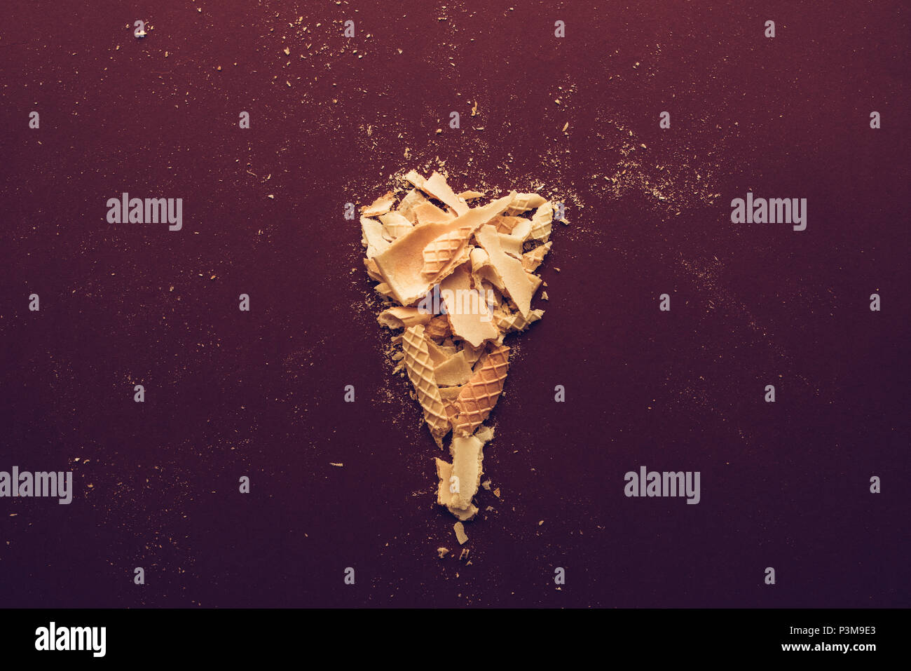 Crushed ice cream cone on dark brown background, flat lay - Stock Image