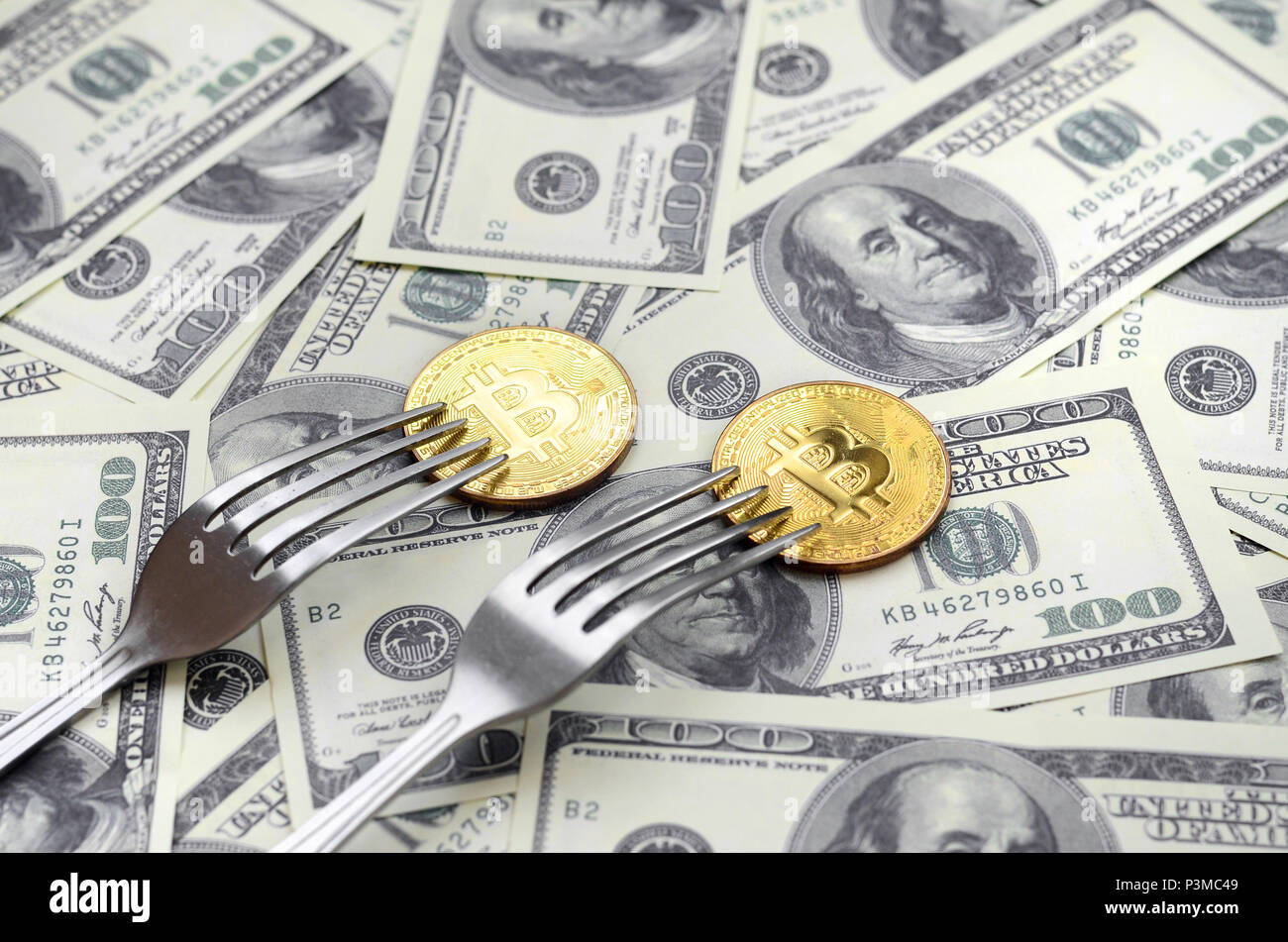 Bitcoin getting New Hard Fork Change, Physical Golden Crytocurrency Coin under the fork on the dollars background. Blockchain Transaction System Crisi - Stock Image