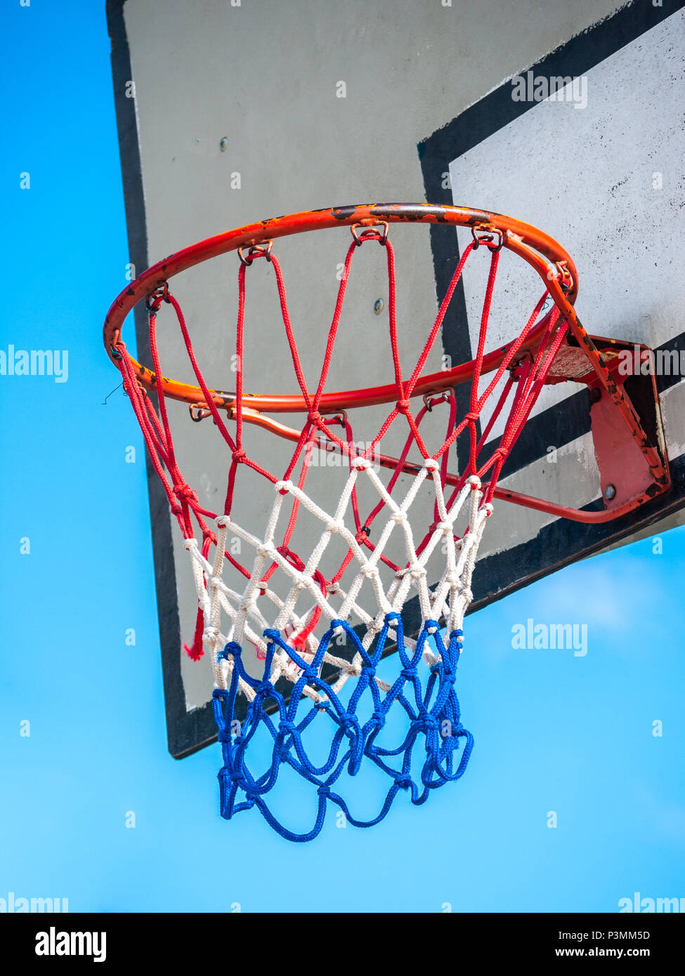Close up of a basketball hoop and backboard against cloudless blue sky - Stock Image