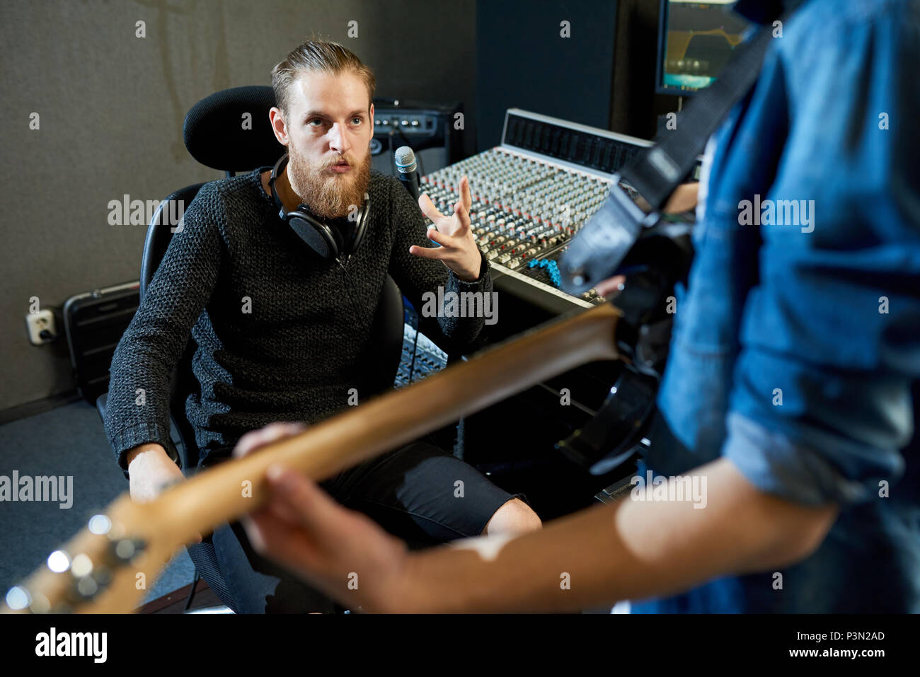 Sound producer talking to musician in studio - Stock Image