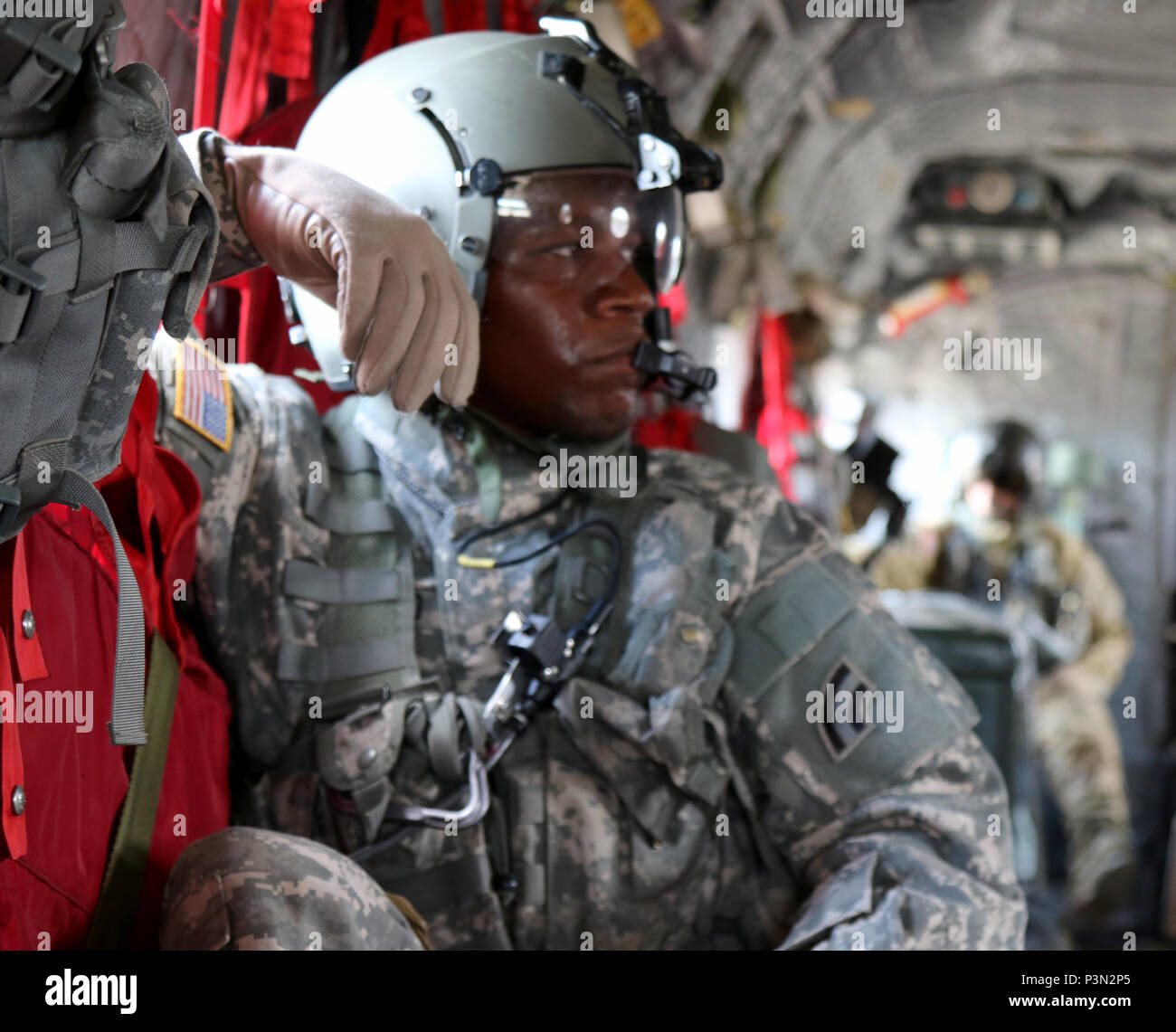 """Maryland National Guard's Sgt. DaShaun Hood, a CH-47 """"Chinook"""" crew chief with B Co, 3rd Battalion, 126th Aviation, monitors in-flight operations during a route familiarization exercise at the Army's Joint Readiness Training Center, Fort Polk, Louisiana, Wednesday, July 13, 2016.  The aviators join more than 5,000 Soldiers from other state Army National Guard units, active Army and Army Reserve troops as part of the 27th Infantry Brigade Combat Team task force.  The Soldiers will hone their skills and practice integrating combat operations ranging from infantry troops engaging in close combat  Stock Photo"""