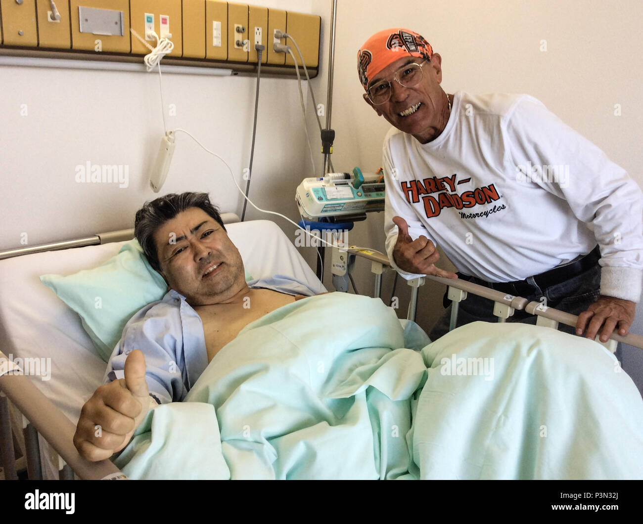 John D. Trent (right), a Defense Commissary Agency contractor and motorcycle enthusiast living in Japan, visits his friend and fellow rider, Makoto Tanabe (left), as he recovers from his injuries sustained in an accident that occurred July 3, 2016, in Shizuoka Prefecture. Trent saved Tanabe's life during a leisure group ride with the Hard n' Fast international riding club. While turning onto a bridge, Tanabe briefly lost control of his bike, hitting the bridge's sidewall and nearly severing his left foot. Trent applied first aid by using a bungee cord as a tourniquet, thereby stopping the blee - Stock Image