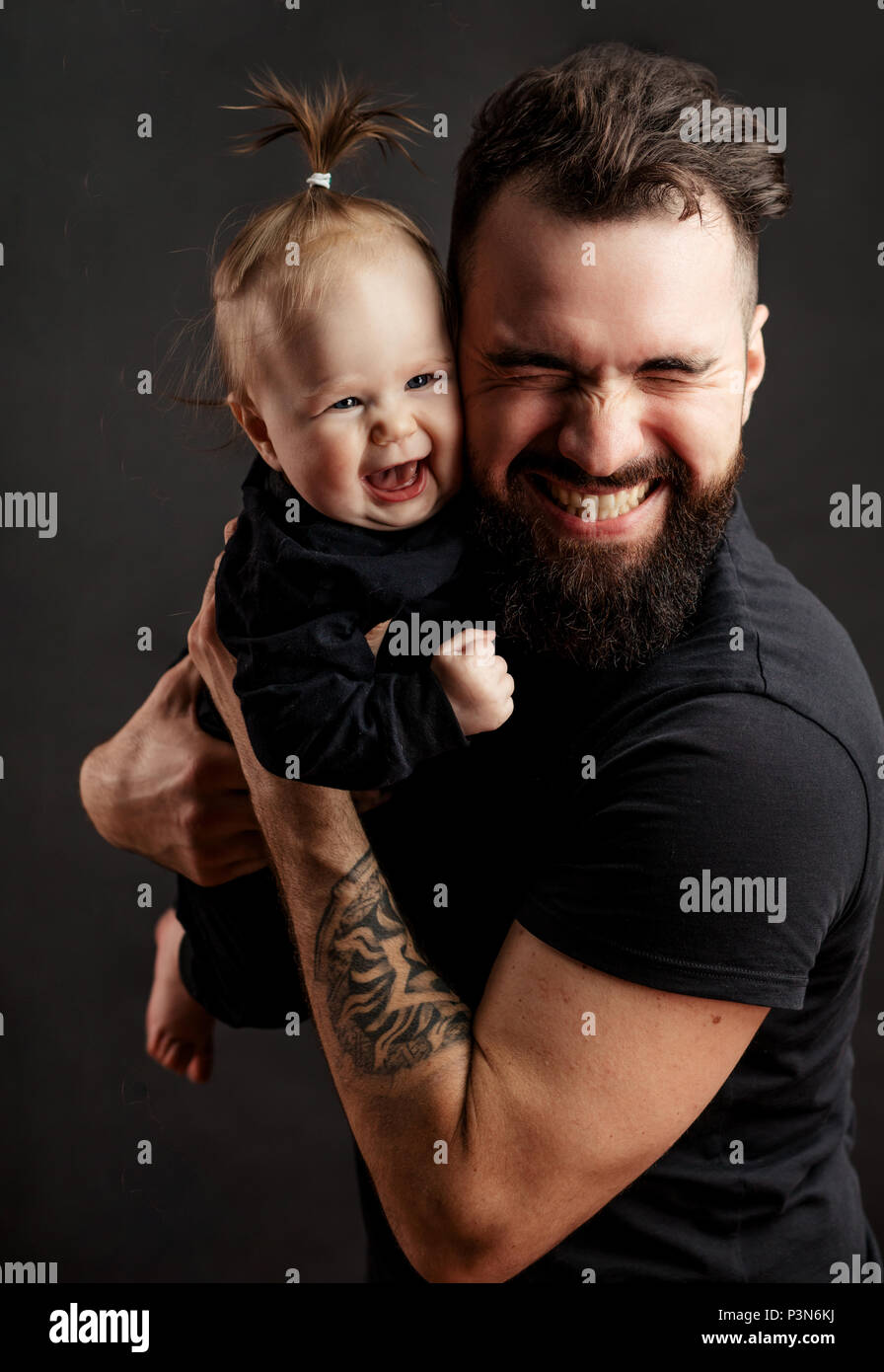 a598bb2424559 Handsome tattooed young man holding cute little baby on black background
