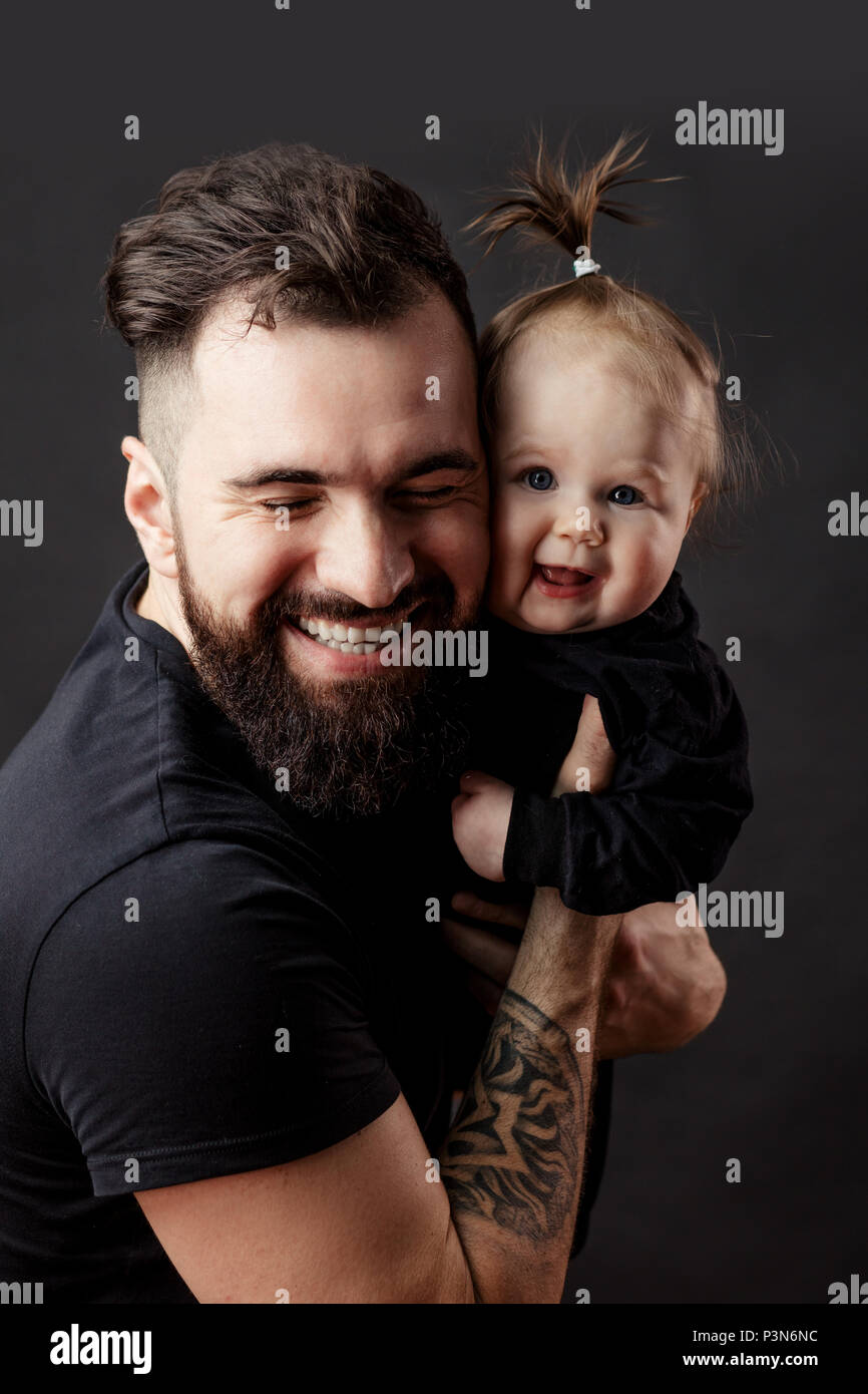 Handsome tattooed young man holding cute little baby on black background Stock Photo