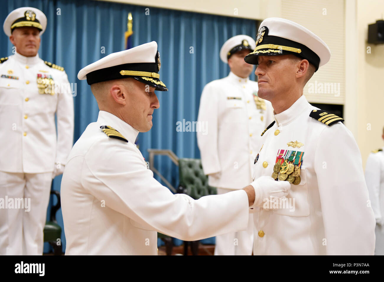 160708-N-DH124-055  OKINAWA, Japan (July 8, 2016) - Commander, 30th Naval Construction Regiment, Capt. Jeffrey Killian places the Meritorious Service Medal on Cmdr. Jeffrey Lengkeek during his change of command ceremony on Camp Shields in Okinawa, Japan, Jul. 8.  Cmdr. James Cho, transferring from Naval Facilities Engineering Command (NAVFAC) Southwest relieved Lengkeek, who has orders to Naval Special Warfare Development Group, as commanding officer of Naval Mobile Construction Battalion (NMCB) 4. (U.S. Navy photo by Mass Communication Specialist 1st Class Rosalie Chang/Released) - Stock Image