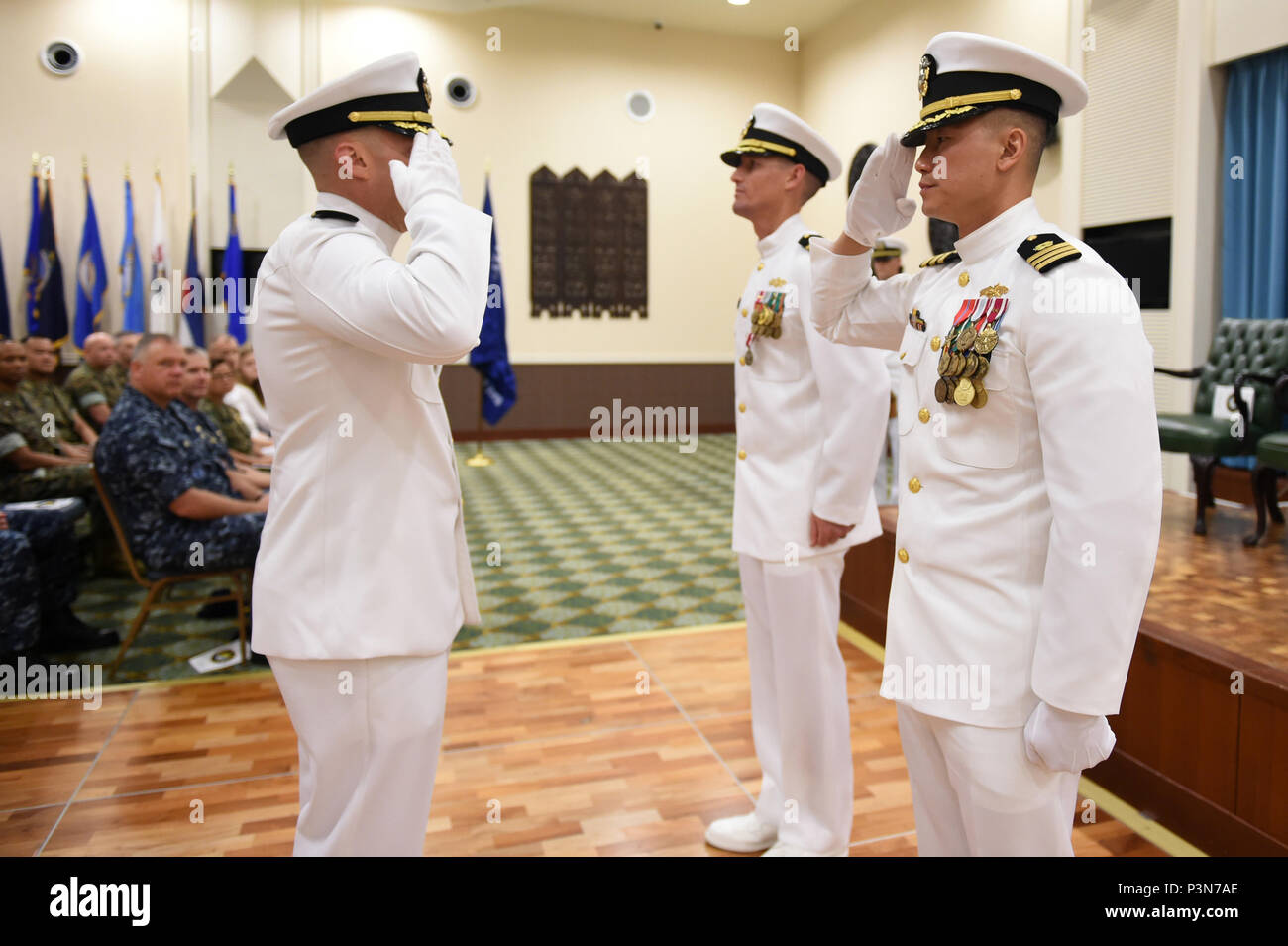 160708-N-DH124-170  OKINAWA, Japan (July 8, 2016) - Cmdr. James Cho salutes Commander, 30th Naval Construction Regiment, Capt. Jeffrey Killian, official taking charge as commanding officer of Naval Mobile Construction Battalion (NMCB) 4 on Camp Shields in Okinawa, Japan, Jul. 8.  Cho transferred from Naval Facilities Engineering Command (NAVFAC) Southwest, serving as the Public Works Officer at Naval Base San Diego.  (U.S. Navy photo by Mass Communication Specialist 1st Class Rosalie Chang/Released) - Stock Image