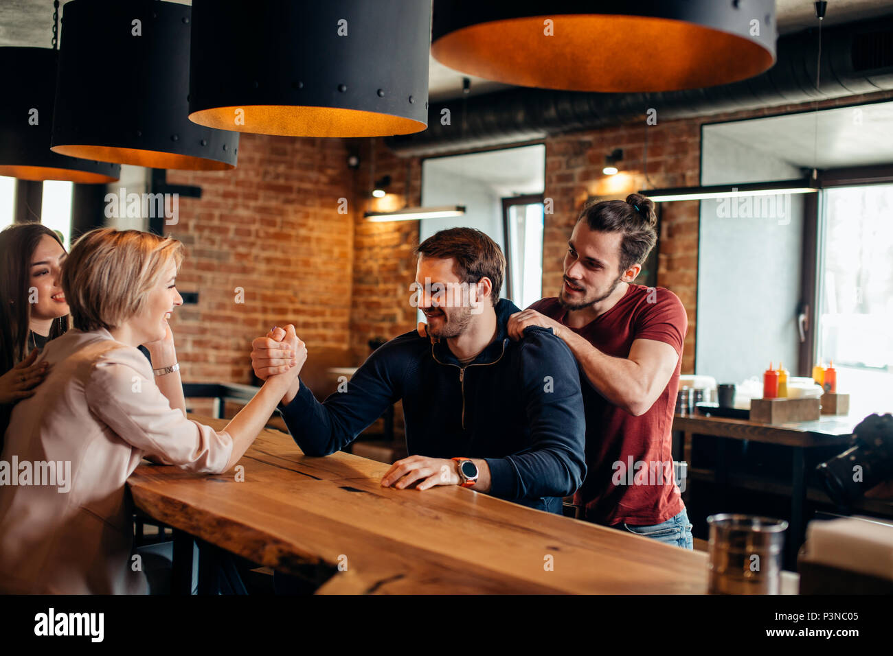 Cheerful gyu and girl having fun arm wrestling each other in pub. - Stock Image