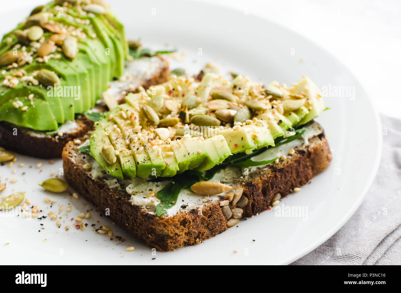 Healthy avocado toasts for breakfast or lunch with rye bread, sliced avocado, arugula, pumpkin and sesame seeds, salt and pepper. Vegetarian sandwiche - Stock Image