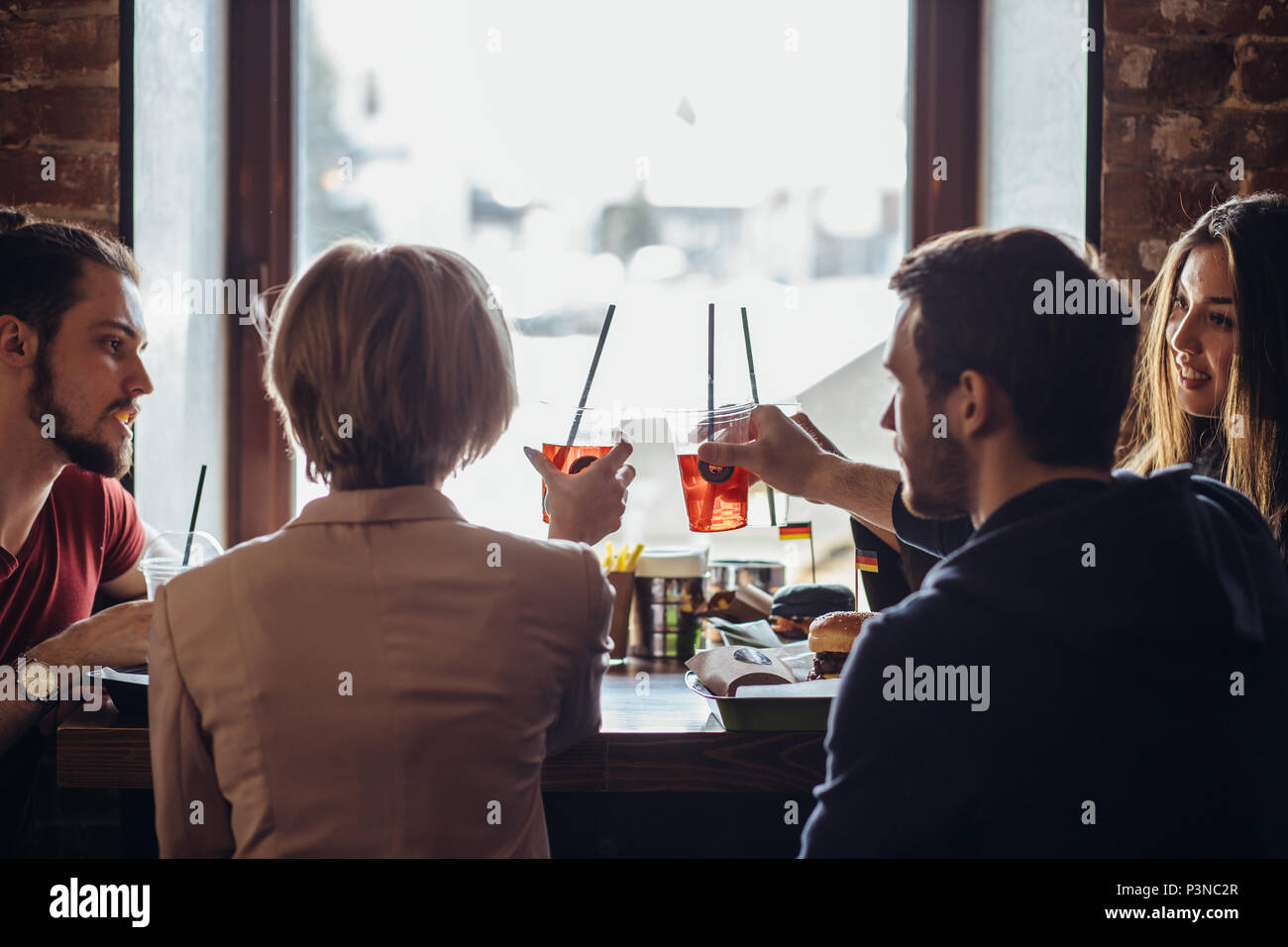 Back view of company of young happy people talking while sitting at cafe Stock Photo