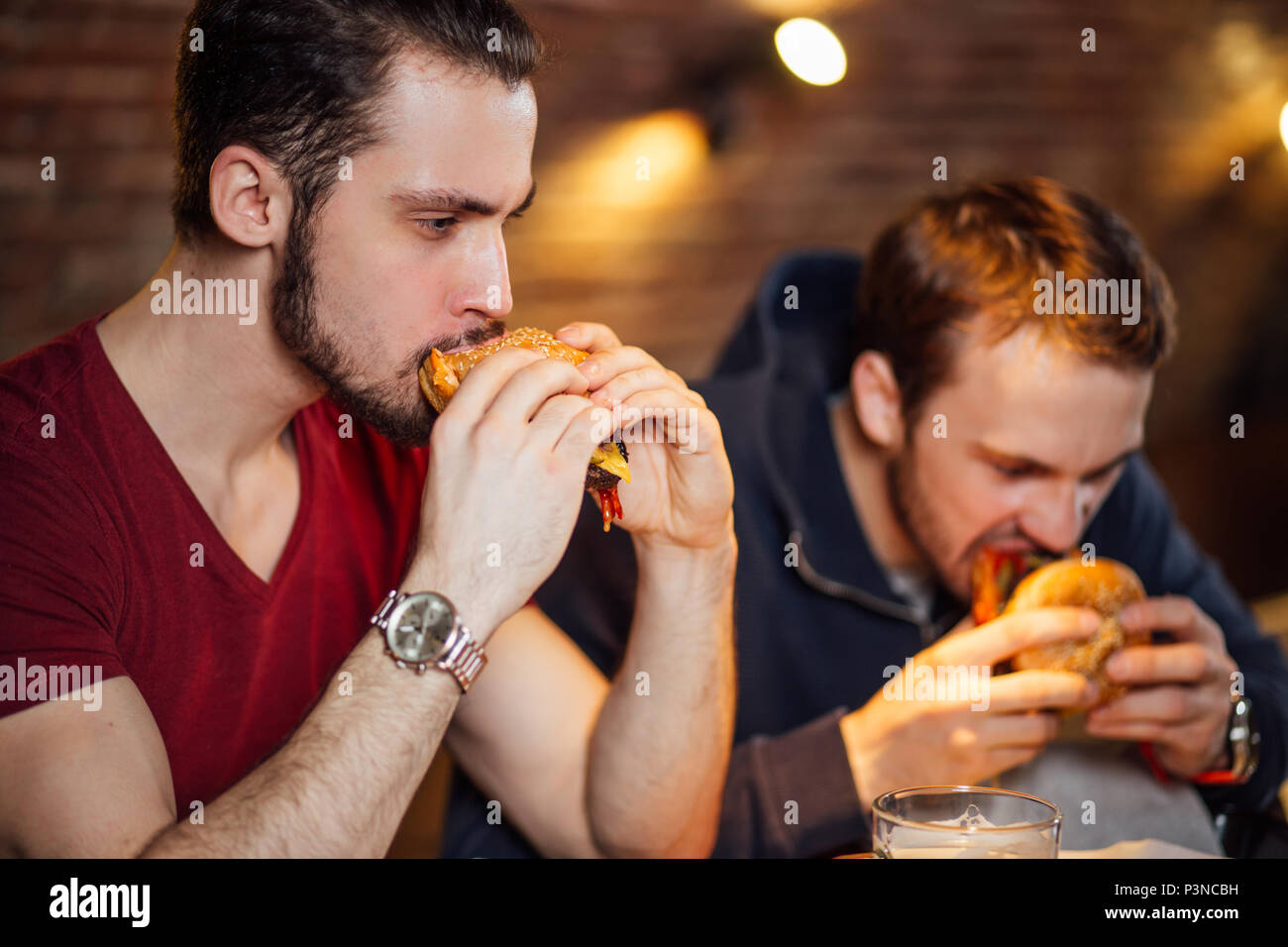 Two happy male friends eating tasty burgers in bar. Stock Photo