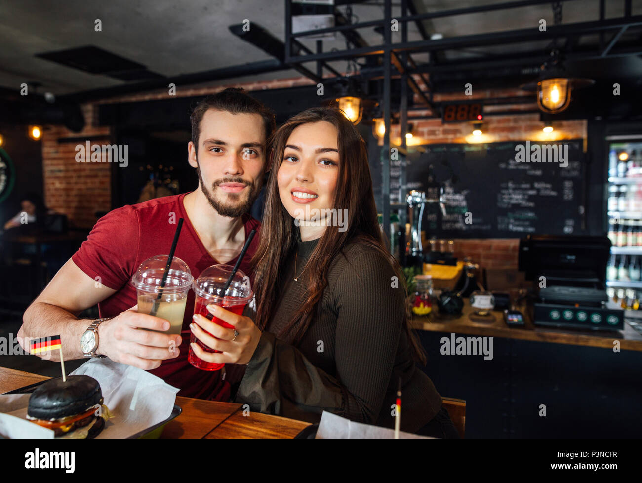 Positive young loving couple meeting in a cafe. - Stock Image