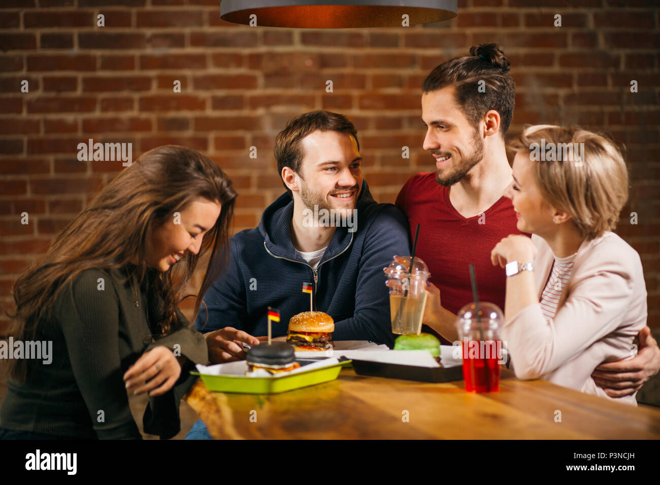 Group Of Young Friends Meeting In Cafe. Stock Photo