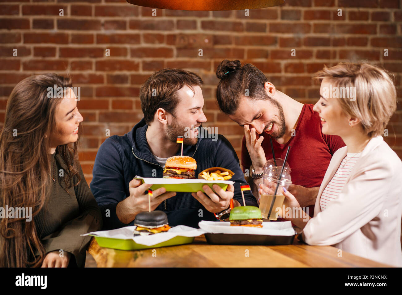Group Of Young Friends Meeting In Cafe. - Stock Image