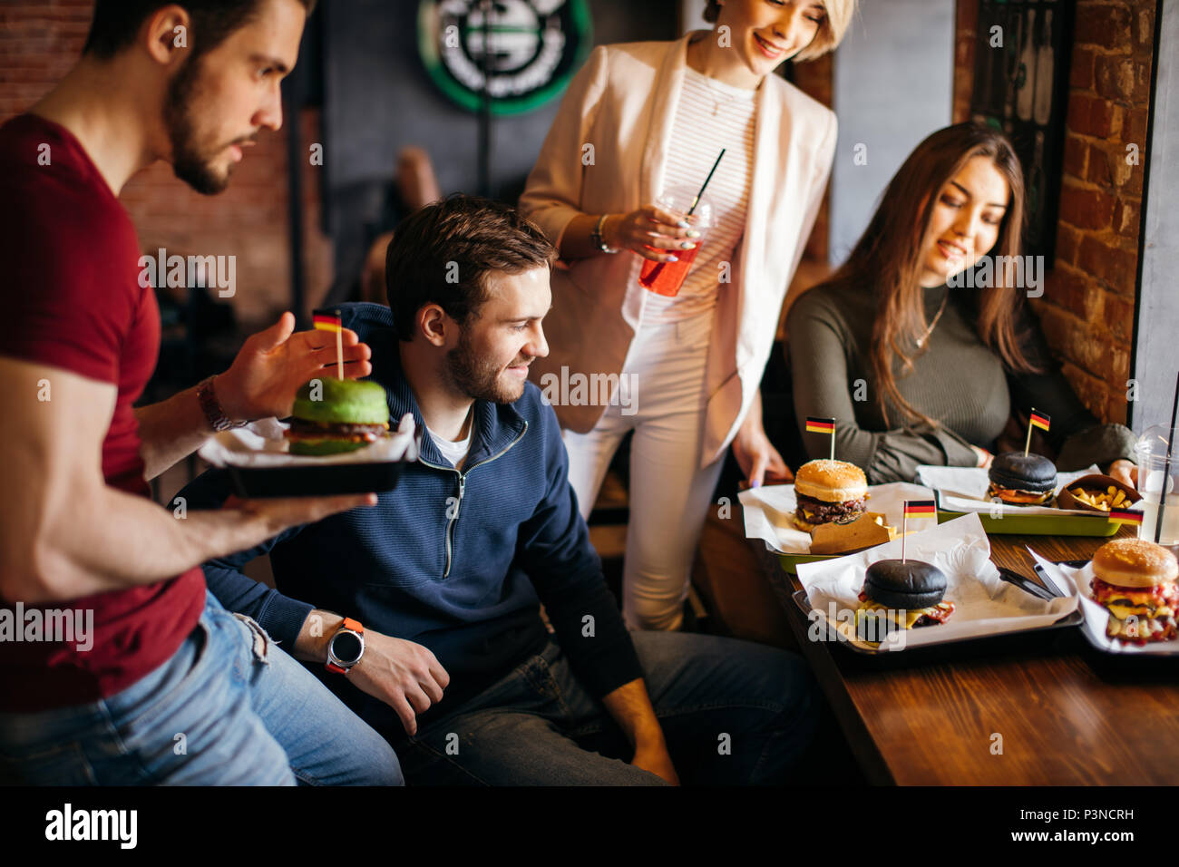 Polite young waiter bringing ordered burgers to guests at restaurant - Stock Image