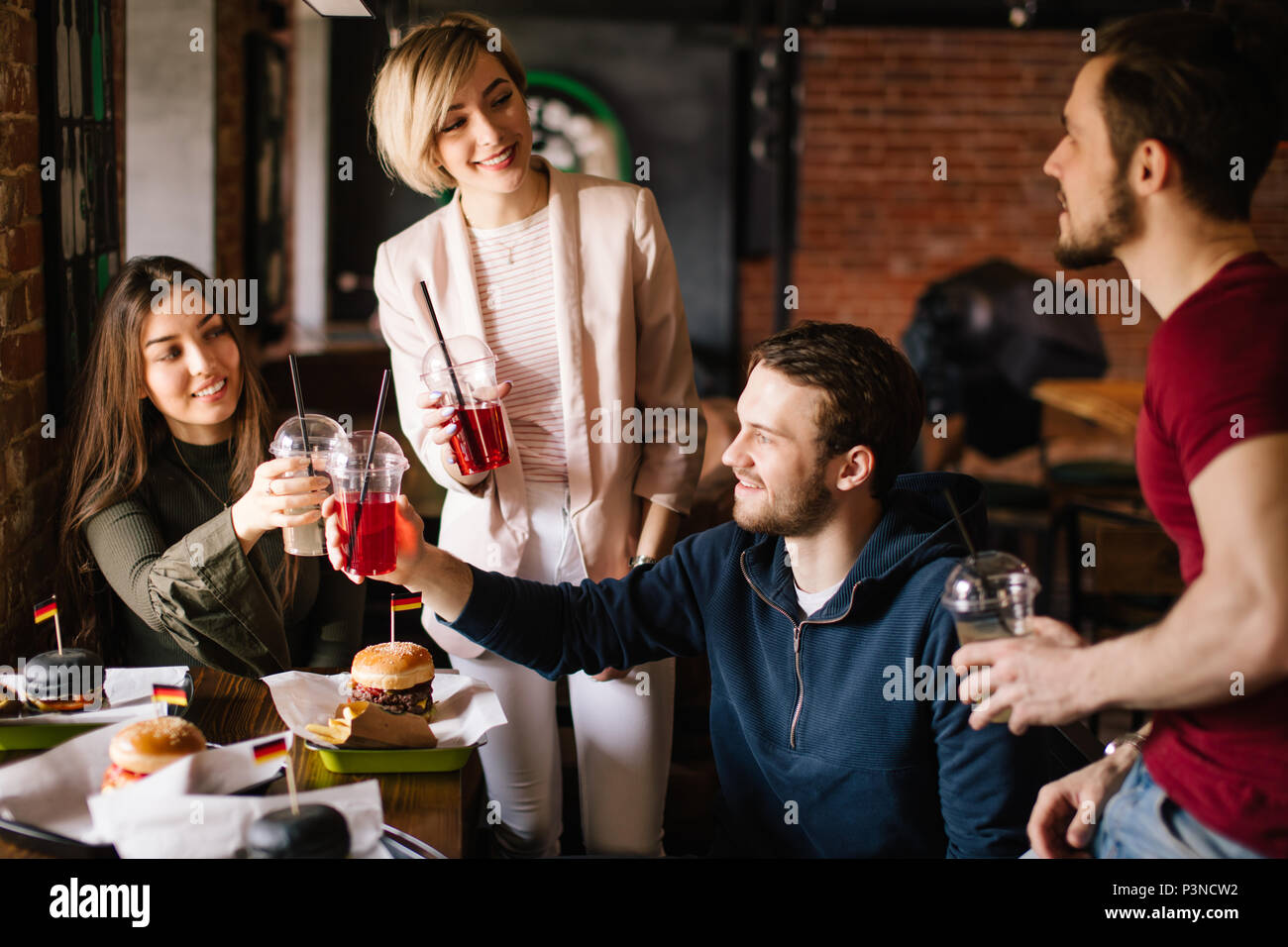 Friends clinking glasses together in a cheer at bar. - Stock Image