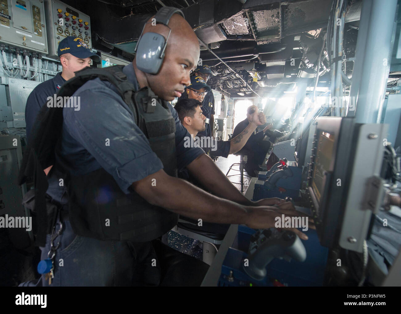 160713-N-DQ503-038    GULF OF ADEN (July 13, 2016) – Gunner's Mate 2nd Class Allen Marshall fires the MK 38 25MM machine gun aboard the guided-missile destroyer USS Roosevelt (DDG 80) during a live-fire exercise. Roosevelt, deployed as part of the Eisenhower Carrier Strike Group, is supporting maritime security operations and theater security cooperation efforts in the U.S. 5th Fleet area of operations. (U.S. Navy Photo by Mass Communication Specialist 3rd Class Taylor A. Elberg/Released) - Stock Image