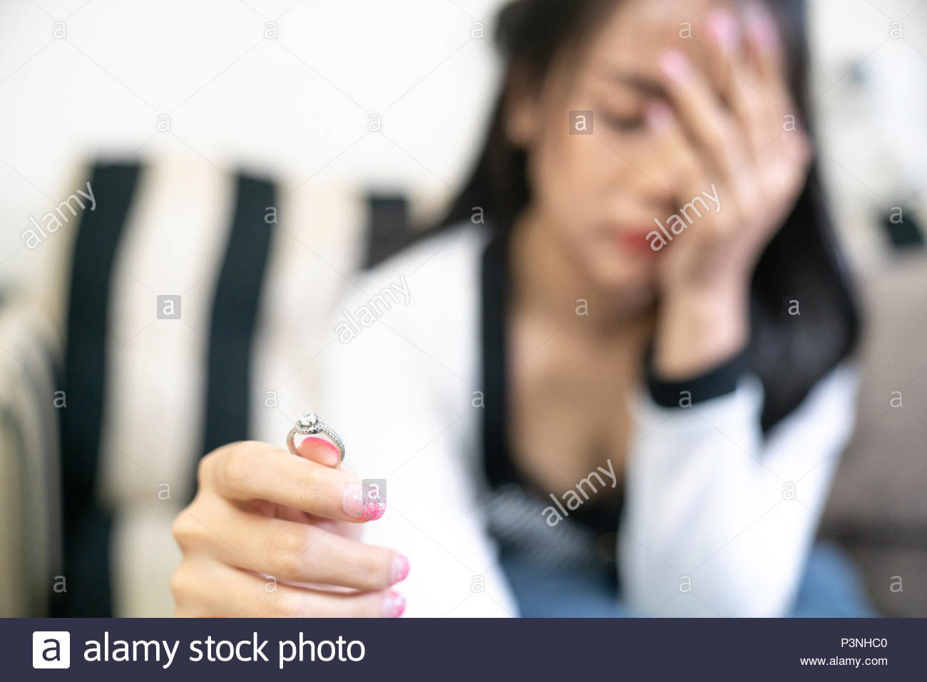 Closeup of a single sad wife after divorce lamenting holding the wedding ring in a house interior - Stock Image