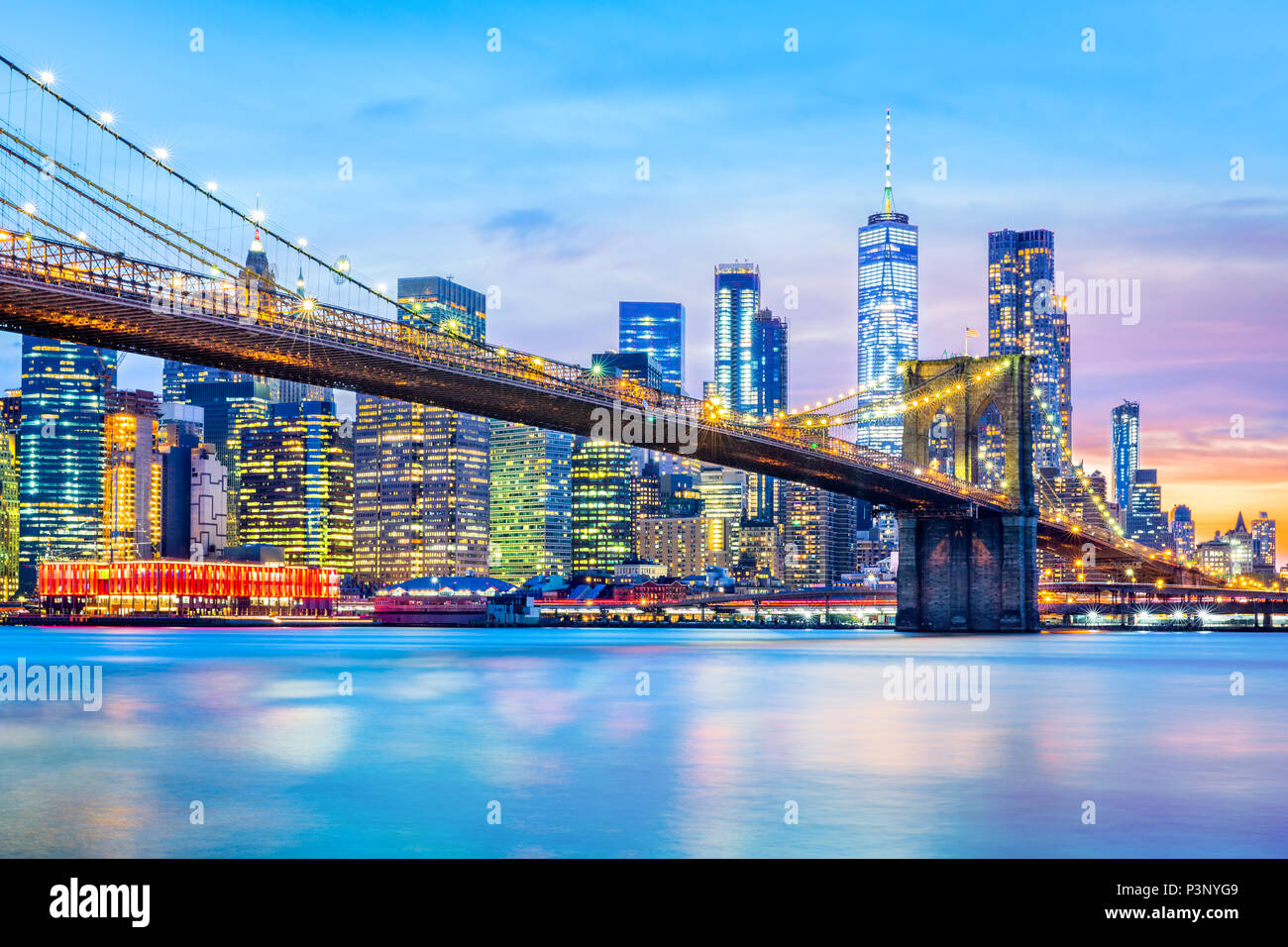 Brooklyn Bridge and the Lower Manhattan skyline at dusk - Stock Image
