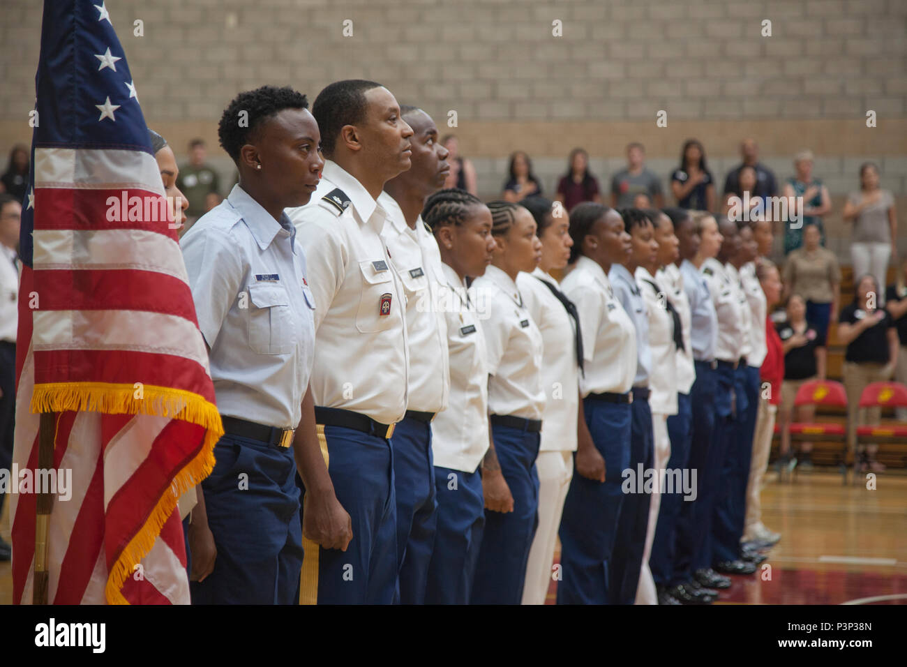 The team representing the United States in the World Military Women's Basketball Championship stand at attention during the National Anthem at the 2016 Conseil International Du Sport Militaire (CISM) opening ceremony on Camp Pendleton, Calif., July 25, 2016. CISM championships are hosted around the world and provide an avenue for the United States to project the positive image with valuable military-to-military engagement through sports. (U.S. Marine Corps photo by Cpl. Tyler S. Dietrich) - Stock Image