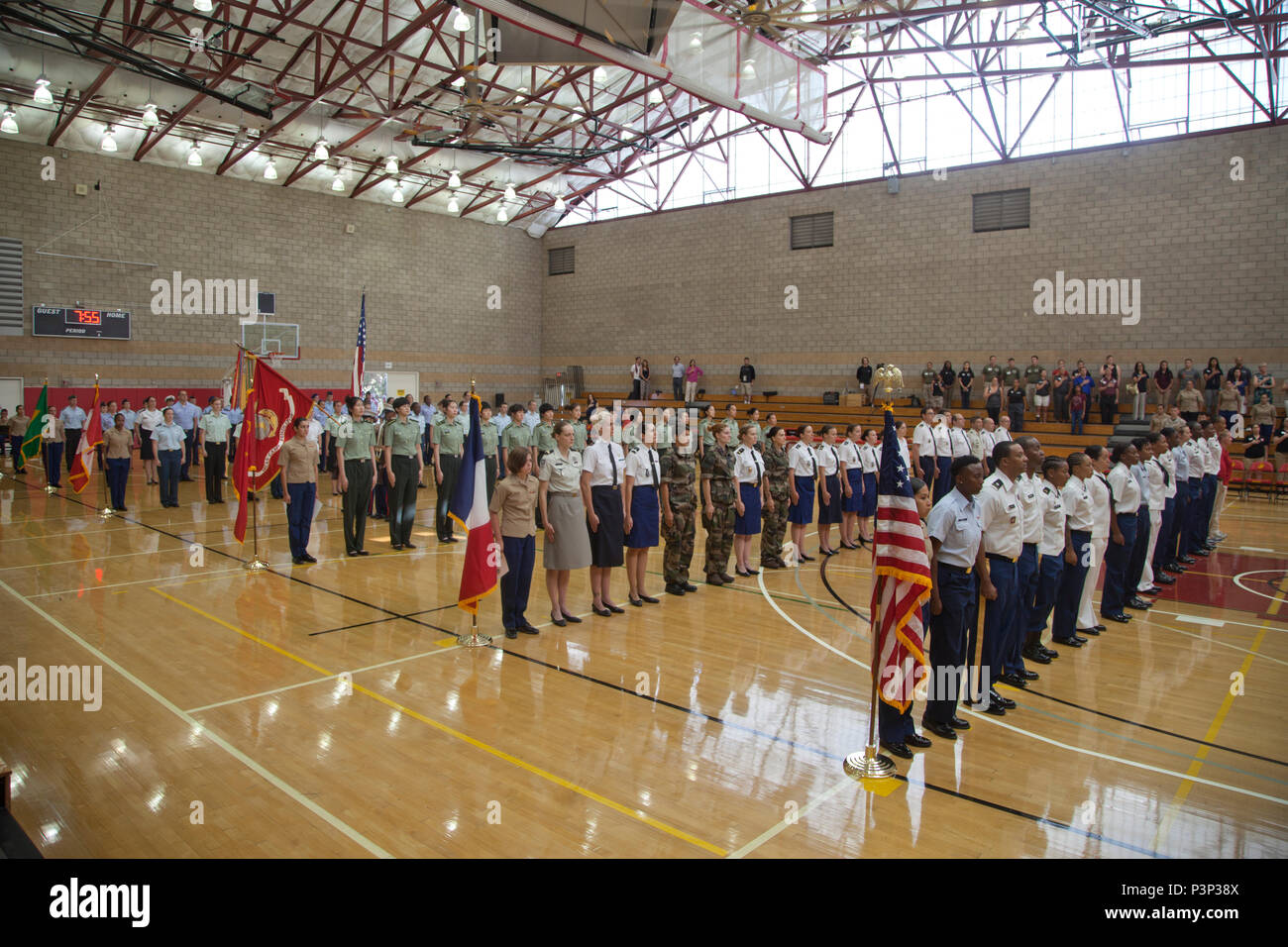 The teams representing the United States, France, China, Canada, Brazil, and Germany in the World Military Women's Basketball Championship stand at attention during the American National Anthem at the 2016 Conseil International Du Sport Militaire (CISM) opening ceremony on Camp Pendleton, Calif., July 25, 2016. CISM championships are hosted around the world and provide an avenue for the United States to project the positive image with valuable military-to-military engagement through sports. (U.S. Marine Corps photo by Cpl. Tyler S. Dietrich) - Stock Image