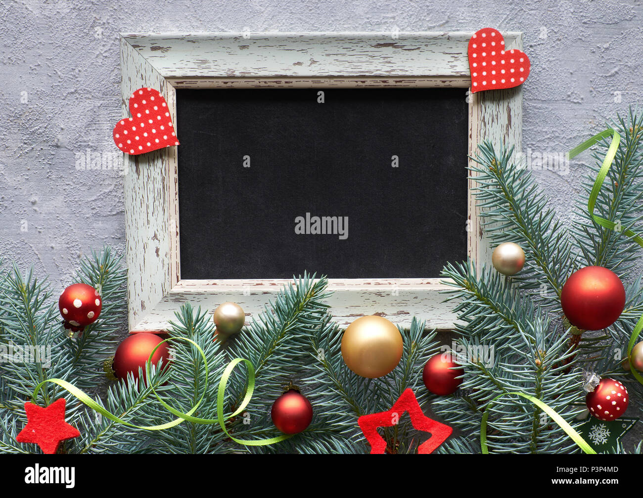 Christmas frame in green and red, top view with text space. Fir twig decorated with baubles, hearts and stars - Stock Image