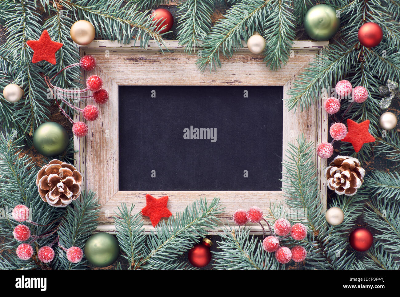 Christmas frame in green and red, top view with text space. Fir twig decorated with baubles, berries and stars - Stock Image