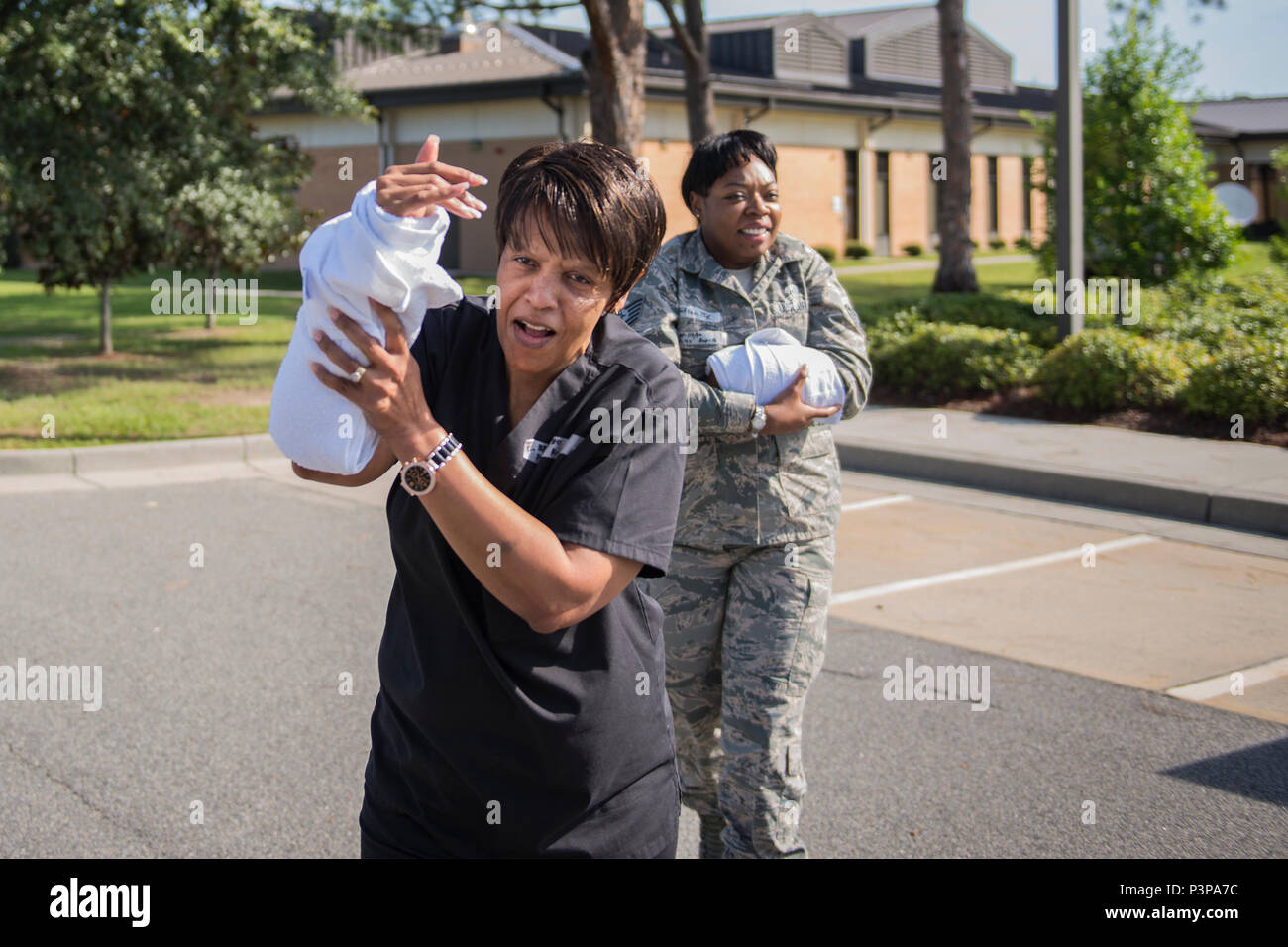 Shelia Davis, 23d Medical Operations Squadron women's health nurse, and U.S. Air Force Tech. Sgt. Ruth Celestine, 23d Medical Support Squadron NCO in charge of medical evaluation boards and patient travel, evacuate a building while also simulating injuries during an active-shooter exercise, July 20, 2016, at Moody Air Force Base, Ga. The 23d Security Forces Squadron responded and simulated neutralizing the threat and securing the area for simulated injured personnel to evacuate. (U.S. Air Force photo by Airman Daniel Snider) - Stock Image