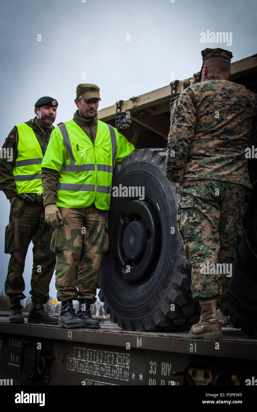 Norwegian Staff Sgt. Cteinar Norli, far left, and Capt. Andre Gjerde speak with U.S. Marine 2nd Lt. Bryan Hassett, right, a logistics officer with 2nd Transportation Support Battalion, Combat Logistics Regiment 2, 2nd Marine Logistics Group, after Marines loaded a 7-ton truck onto a railcar in Hell, Norway, May 9, 2017. The railhead operations were conducted as part of Strategic Mobility Exercise 17 (STRATMOBEX). STRATMOBEX focused on the operational readiness and mobility of equipment in Norway. Stock Photo
