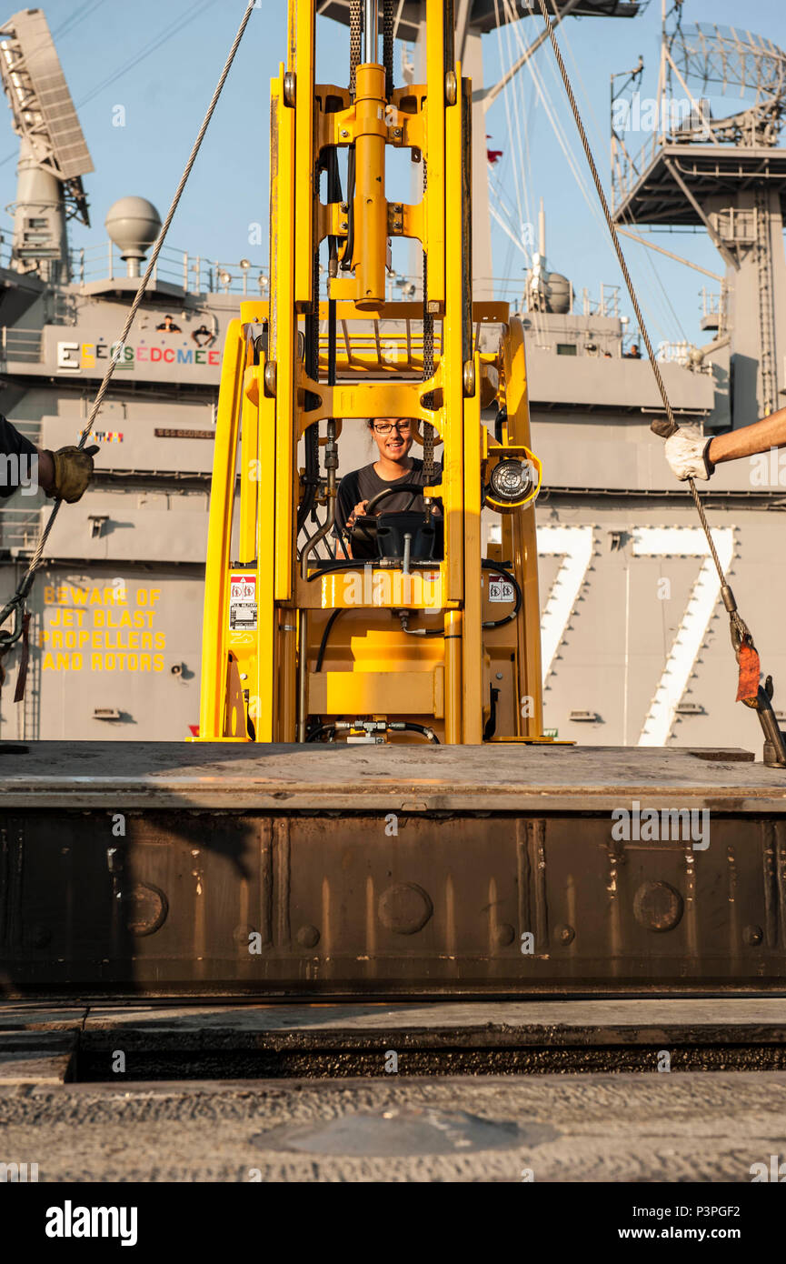 160723-N-FF224-034 ELIZABETH RIVER, Va. (July 23, 2016) Aviation Boatswain's Mate (Equipment) 3rd Class Danity moves equipment on the flight deck of USS George H. W. Bush (CVN 77) as the ship leaves Norfolk Naval Shipyard (NNSY) after completing a 13-month planned incremental availability. GHWB will now conduct sea trials in collaboration with NNSY to evaluate Sailors' performance in addition to testing equipment and systems. After a successful completion, GHWB will return to her homeport of Norfolk, Virginia, and enter a training and qualification cycle in preparation for a 2017 deployment. ( - Stock Image