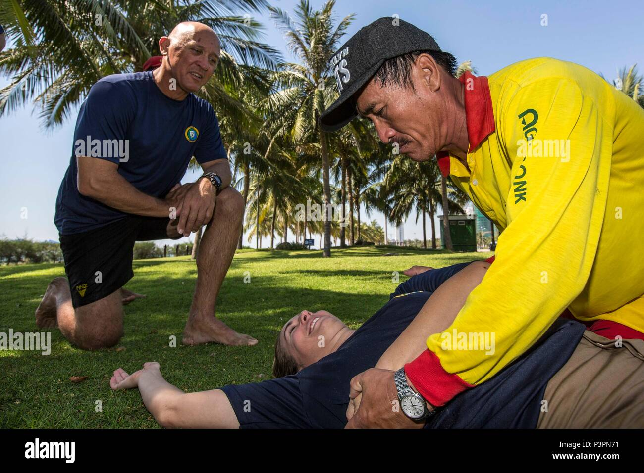 160721-N-CV785-101 DA NANG, Vietnam (July 21, 2016) Australian Army personnel Capt. Peter Conrad (left) and Sgt. Kate Hall instruct cardiopulmonary resuscitation techniques to a Vietnamese lifeguard, during a community relation event, as part of Pacific Partnership 2016. Community relation events bring together the local community and Pacific Partnership personnel and are an essential component of the mission that allow for direct engagement. Partner nations are working side-by-side with local organizations to conduct cooperative health engagements, community relation events and subject matter - Stock Image
