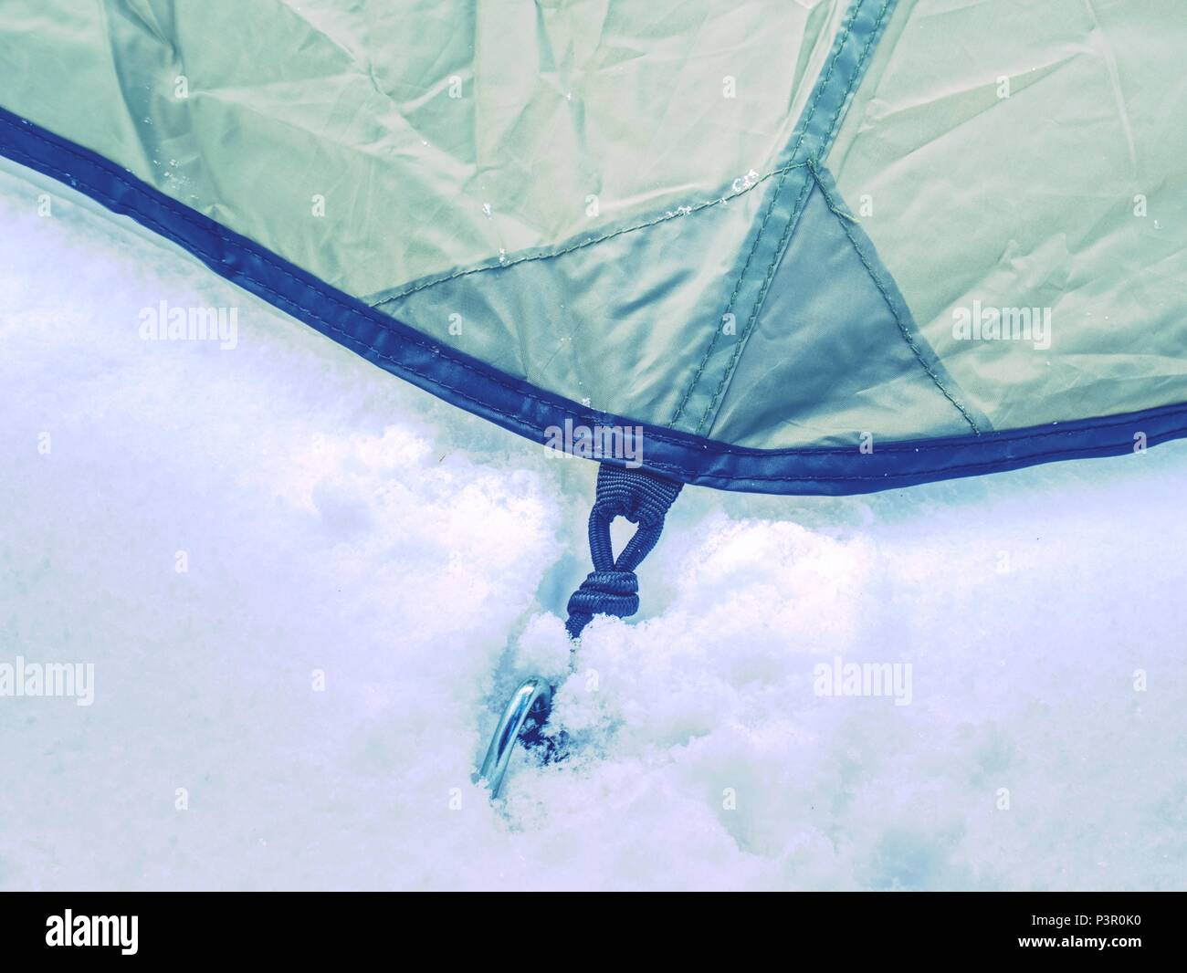 Detail of camping tent anchored in snow. Extreme winter trek. Aluminum Tent Poles and rainfly. - Stock Image