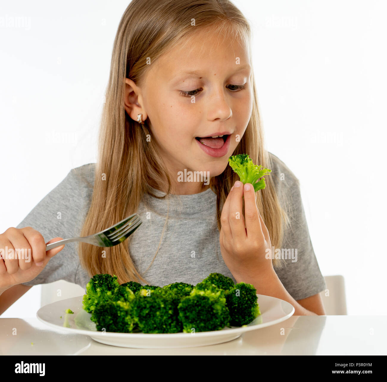895428cb happy young blonde girl with thumbs up enjoying and loving eating her broccoli  vegetables on a