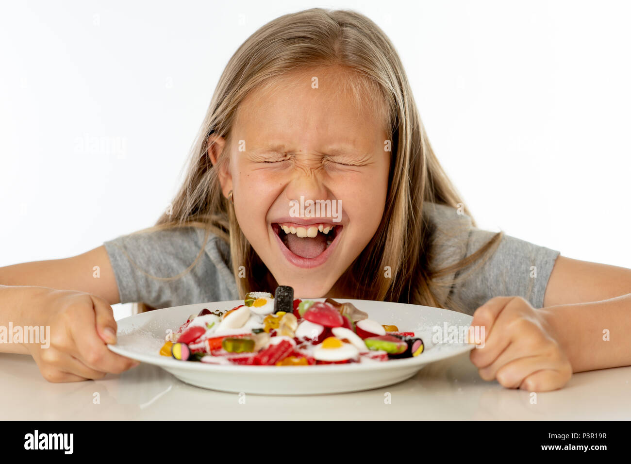 pretty happy sugar high caucasian female child eating dish full of candy holding fork and knife in sweet sugar abuse dangerous diet and unhealthy nutr - Stock Image