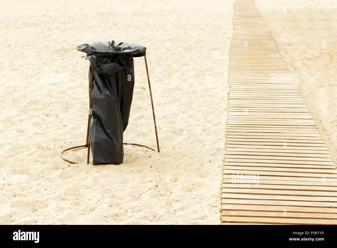 homemade Garbage container from a garbage bag on the beach. - Stock Image