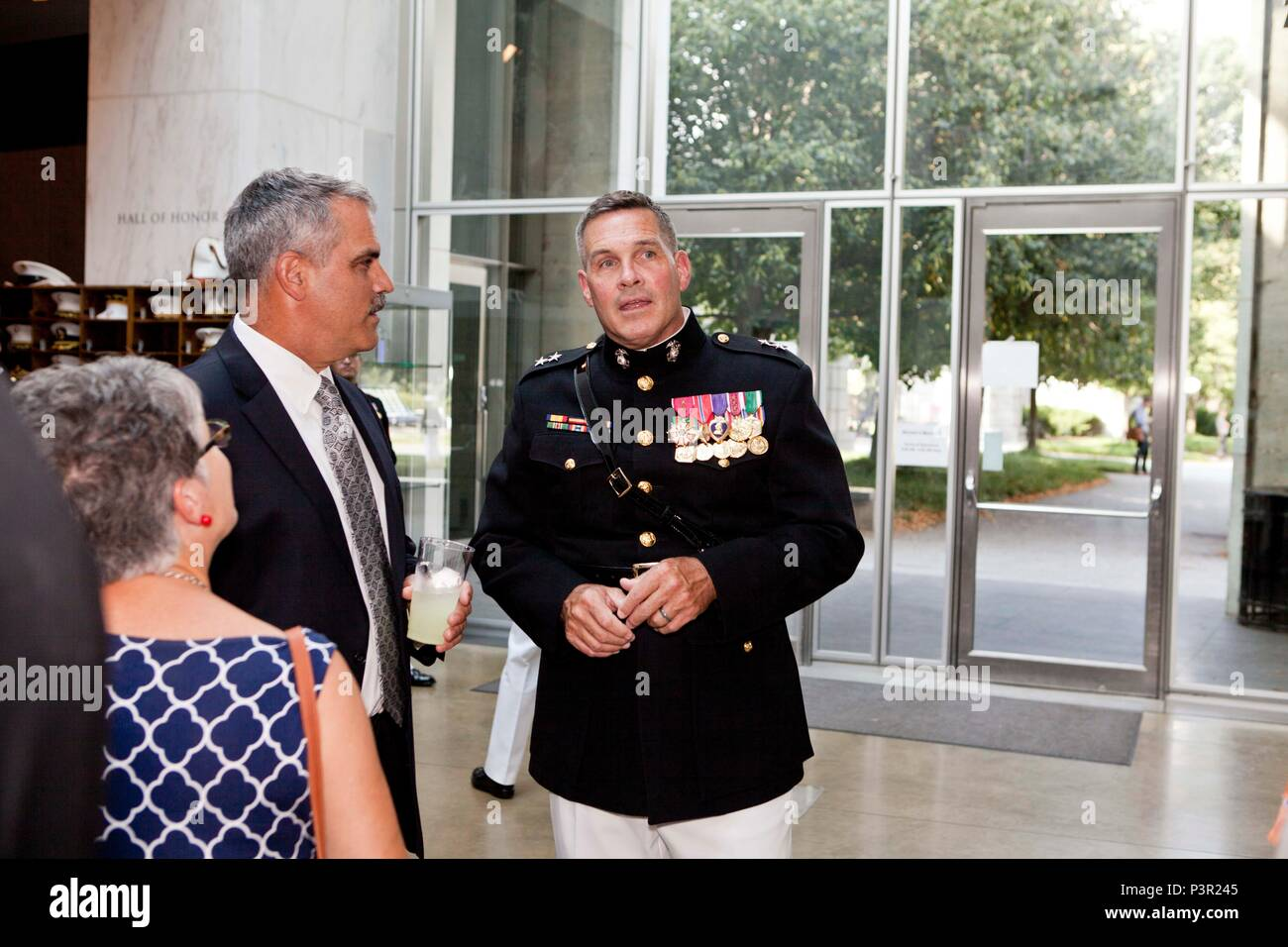 U.S. Marine Corps Maj. Gen. John Ewers, right, staff judge advocate to the commandant of the Marine Corps, speaks with retired U.S. Marine Corps Col. Ray Damm during the sunset parade reception at the Women in Military Service for America War Memorial, Arlington, Va., July 19, 2016. Sunset parades are held as a means of honoring senior officials, distinguished citizens and supporters of the Marine Corps. (U.S. Marine Corps photo by Lance Paul A. Ochoa) Stock Photo