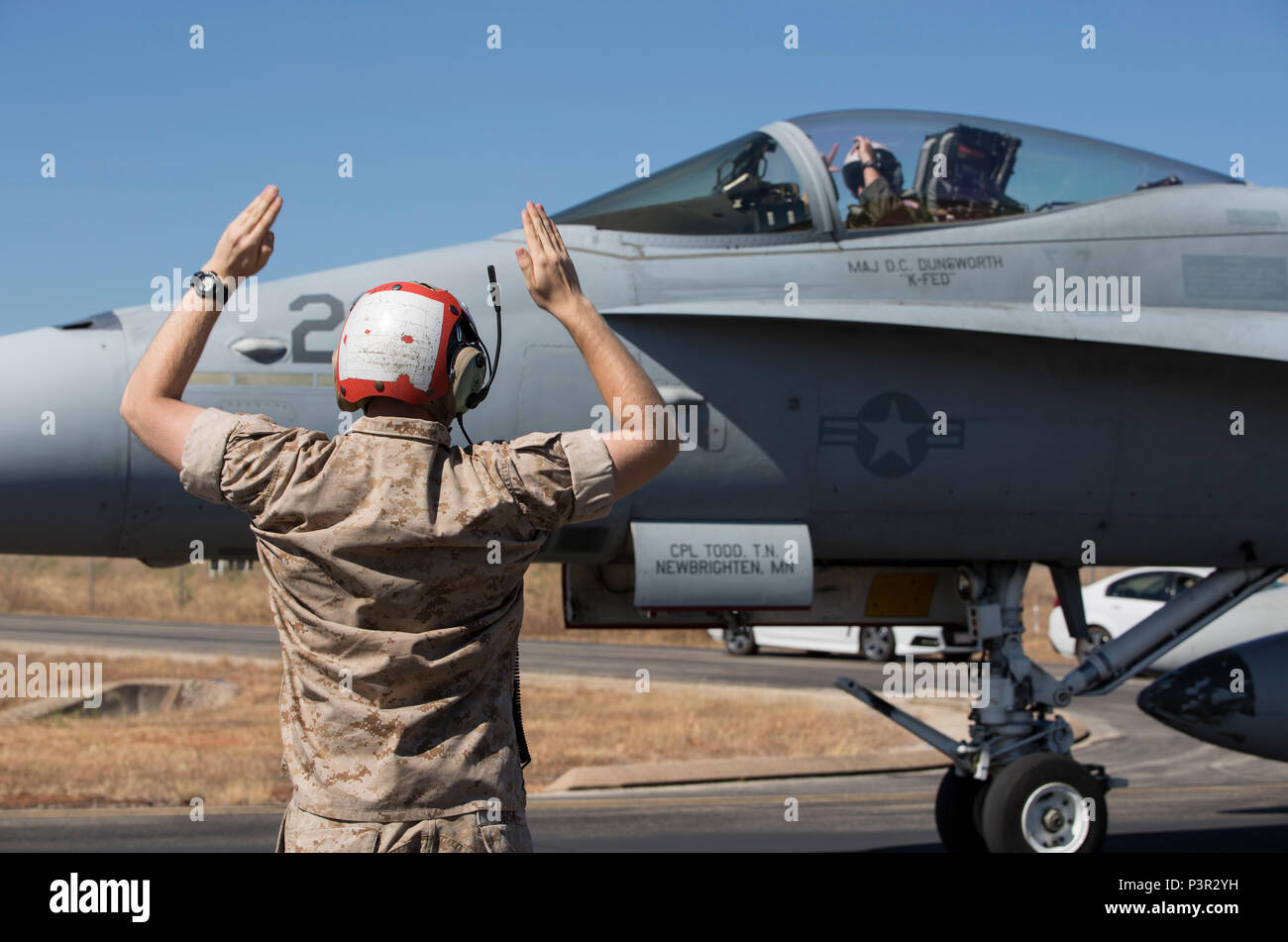 Cpl. Matthew Sisk, ordnance man with Marine Fighter Attack Squadron (VMFA) 122, guides an F/A 18C Hornet with VMFA-122 to a halt for inspection at Royal Australian Air Force Base Tindal, Australia, July 22, 2016. VMFA-122 traveled to RAAF Base Tindal for the first time for exercises Southern Frontier Unit Level Training and Pitch Black 16. Southern Frontier ULT will help the squadron gain experience and qualifications in low altitude, air ground, high explosive ordnance delivery at the unit level. Pitch Black 16 affords Marines with VMFA-122 the opportunity to integrate and increase interopera - Stock Image