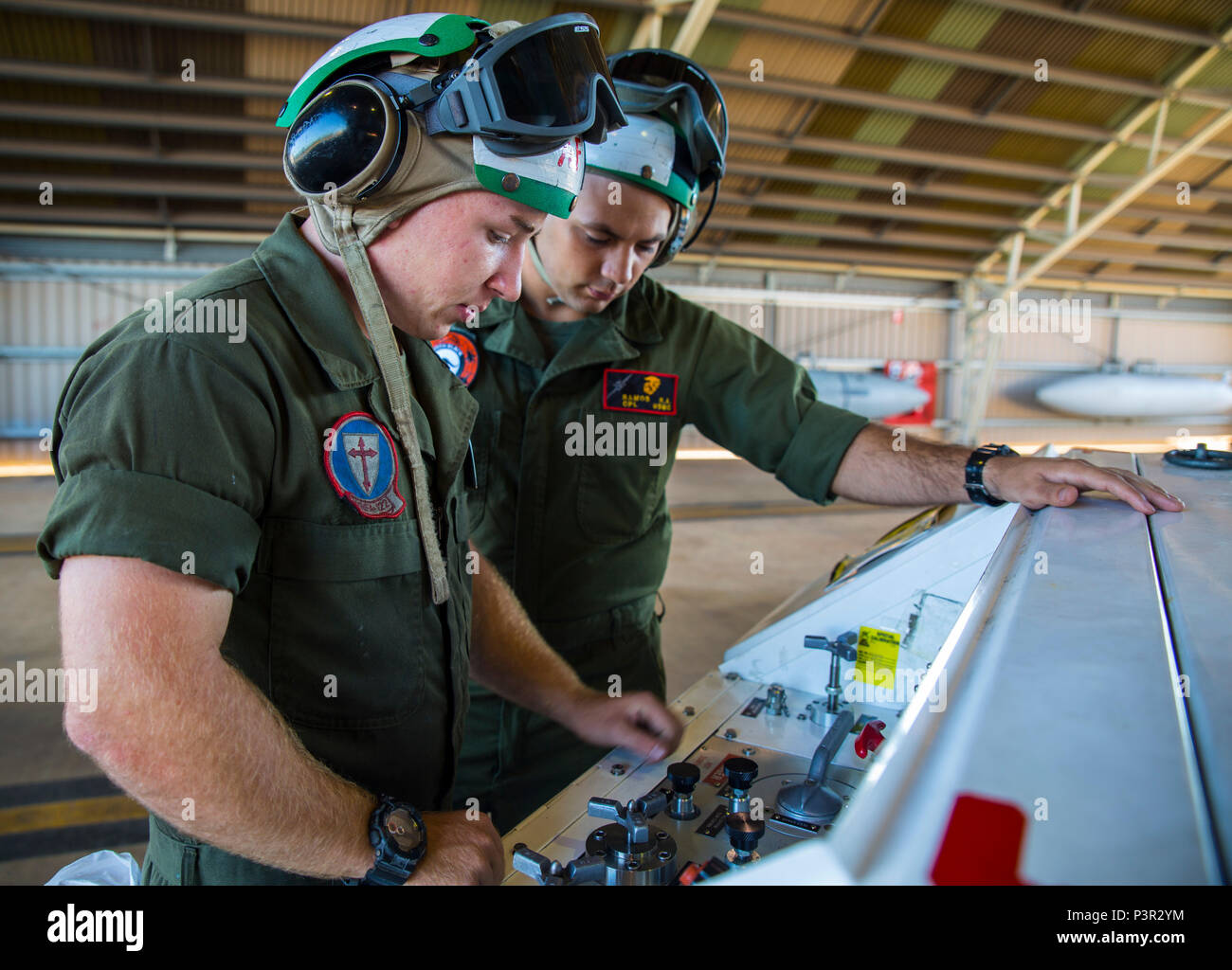 Lance Cpl. James Headrick, an airframe Marine with Marine Fighter Attack Squadron (VMFA) 122, demonstrates how to operate an NC-10 Hydraulic Generator for Cpl. Robert Ramos, Marine Aviation Logisitsics Squadron (MALS) 12 airframes, at Royal Australian Air Force Base Tindal, Australia, July 25, 2016. VMFA-122 traveled to RAAF Base Tindal for the first time to participate in Pitch Black 2016 and unit level training known as Southern Frontier. Pitch Black affords Marines with VMFA-122 the opportunity to integrate and increase interoperability with regional joint and coalition partners, while deve - Stock Image