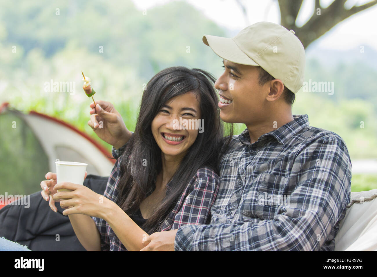 asian couple having barbecue skewers  - Stock Image